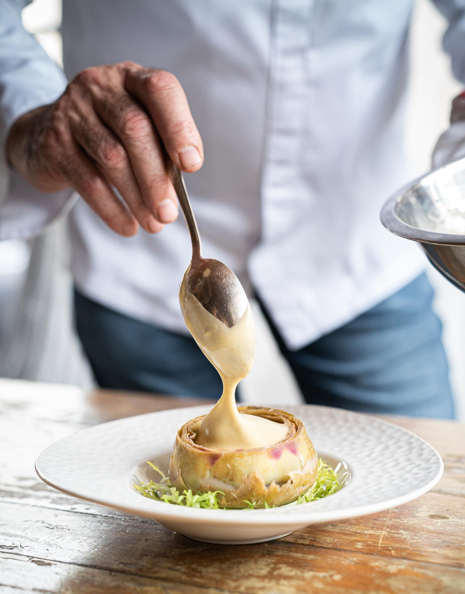 chef Didier Leroy close up of plating his meal on wood table scooping filling with spoon by Bruno Florin for Van Houtte 100th anniversary