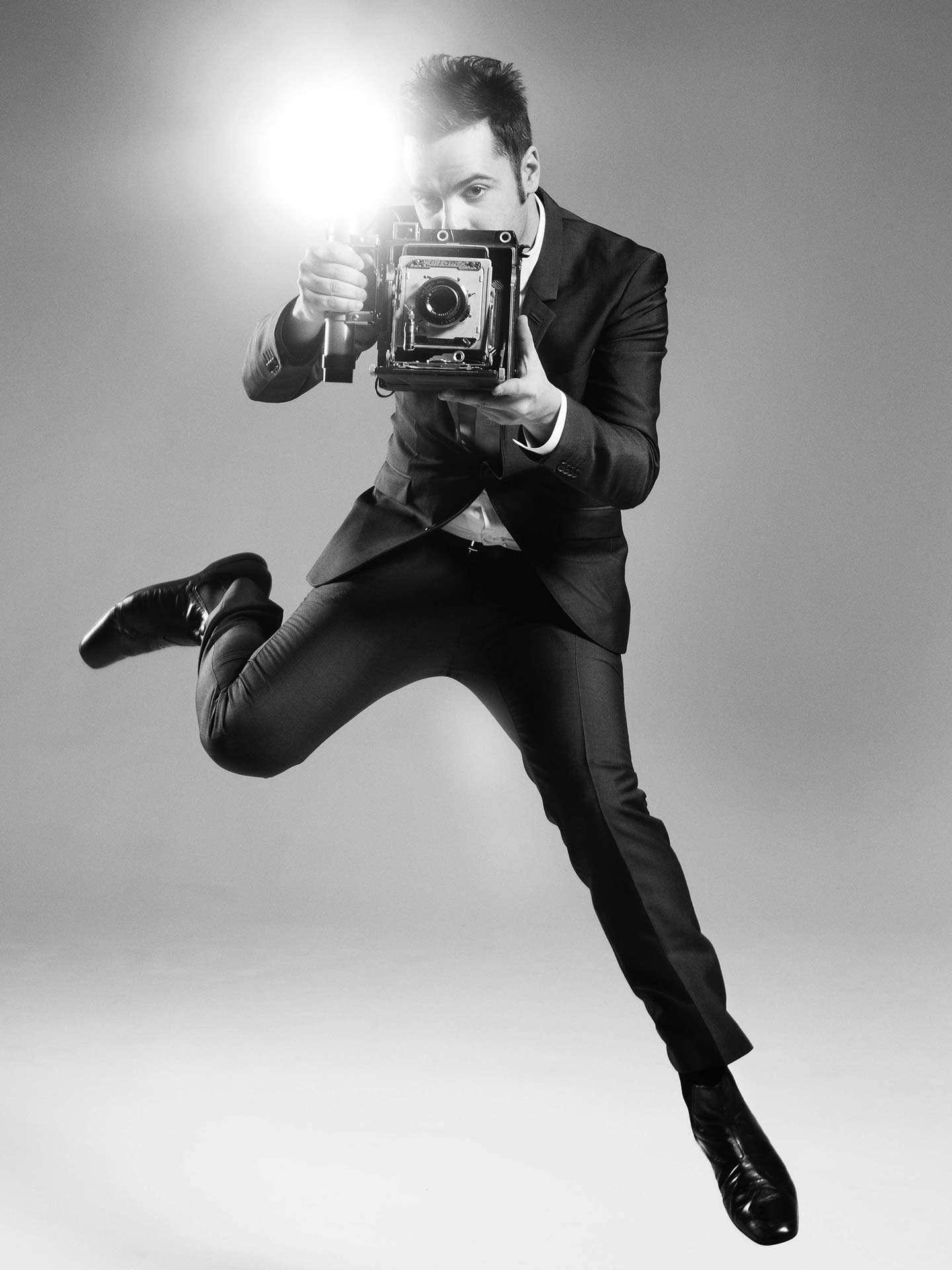 man jumping holding old school camera by Jocelyn Michel