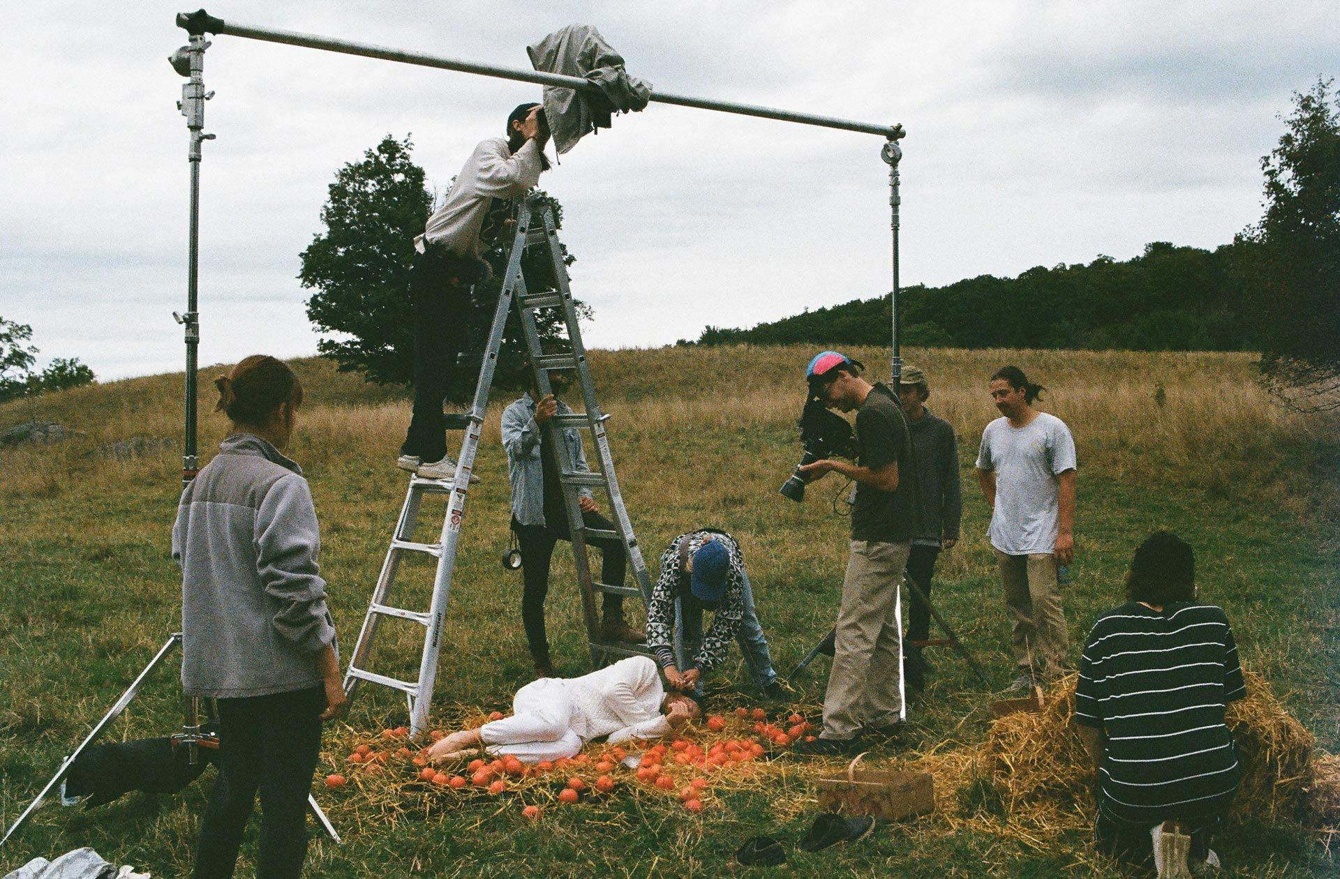 Vincent Ruel-Cote and Marco Gilbert from Les Gamins filming girl laying on the ground on hay and small pumpkins