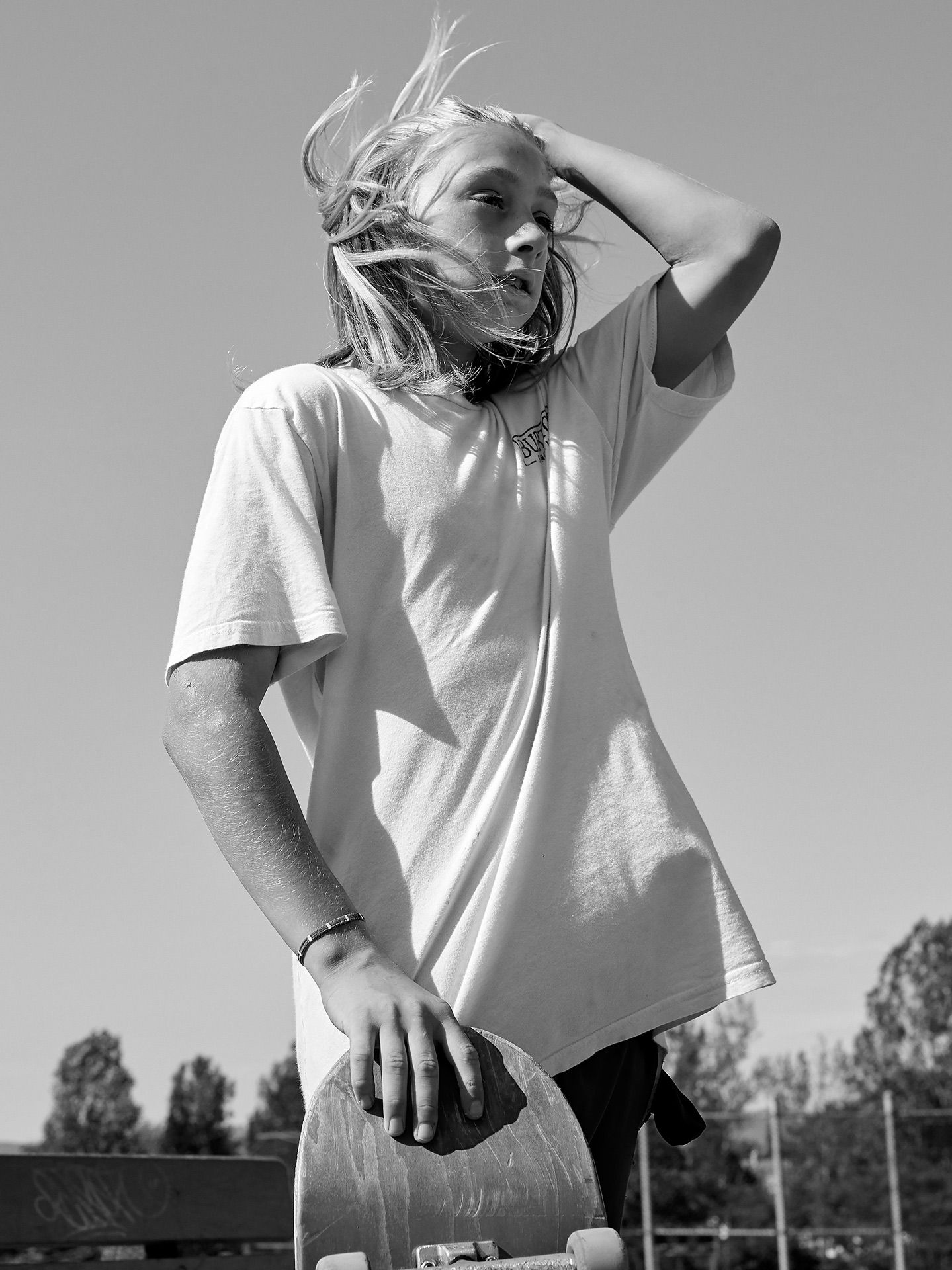 young boy in black and white holding skateboard hair in the wind wearing white shirt by Guillaume Simoneau