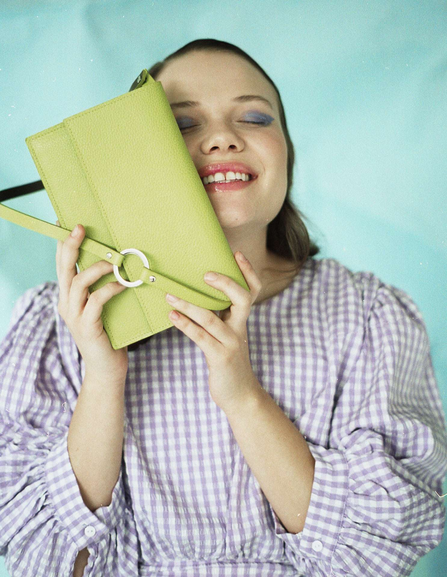 girl smiling holding an almond green purse against her face on light blue background