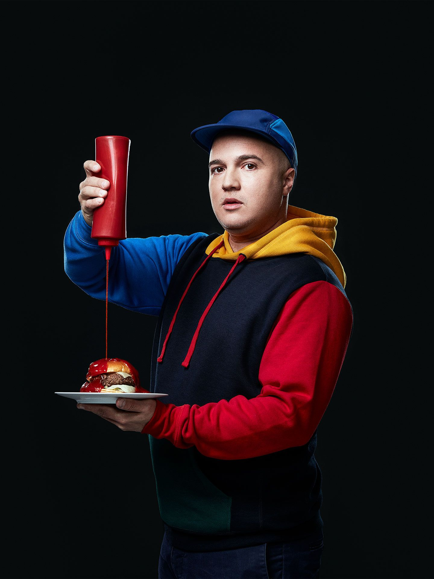 portrait of chef Younes Bengeloune dressed in colourful hoodie squeezing a bottle of ketchup on a burger looking surprised by Jocelyn Michel for the Cathcart