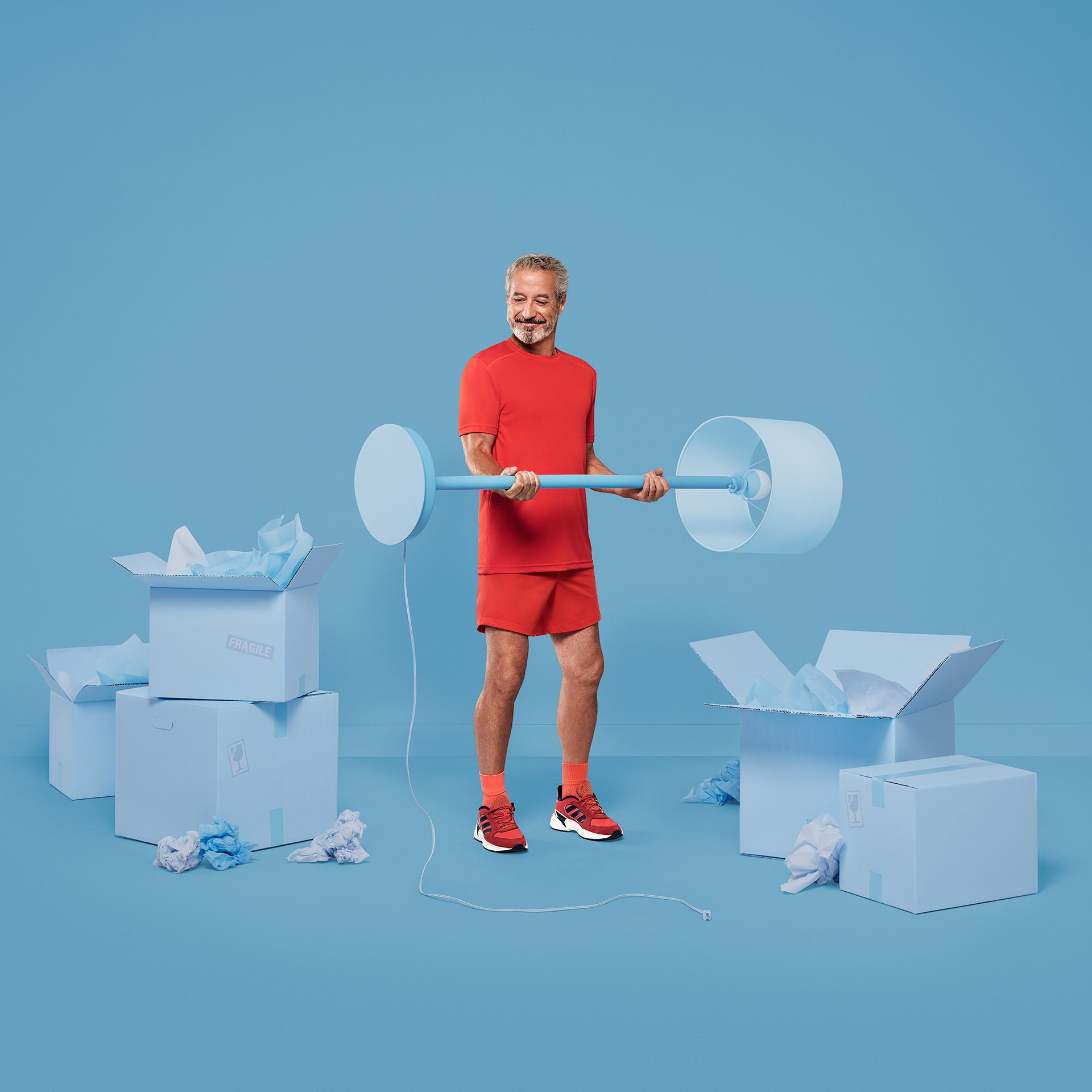 white male using lamp as weight dressed in red on blue background for YMCA by Jocelyn Michel