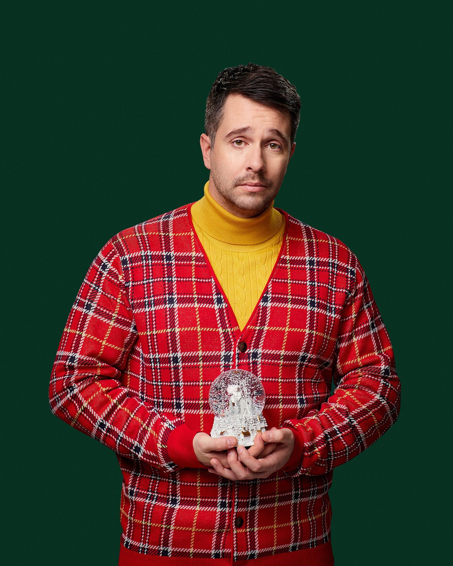 picture of humorist Alexandre Barrette dressed awkwardly in yellow sweater pleated cardigan snowglobe in hand for show semi-croquant by Jocelyn Michel