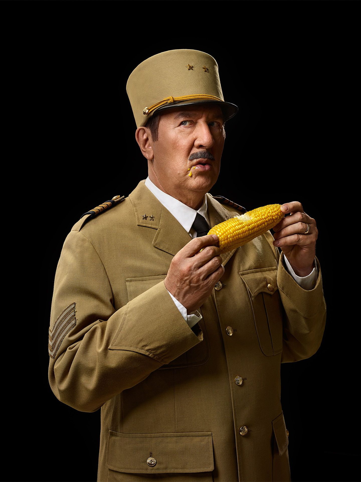 portrait of Gilles Renaud dressed as Charles De Gaulle eating corn on the cob by Jocelyn Michel for Voir Guide Restaurants