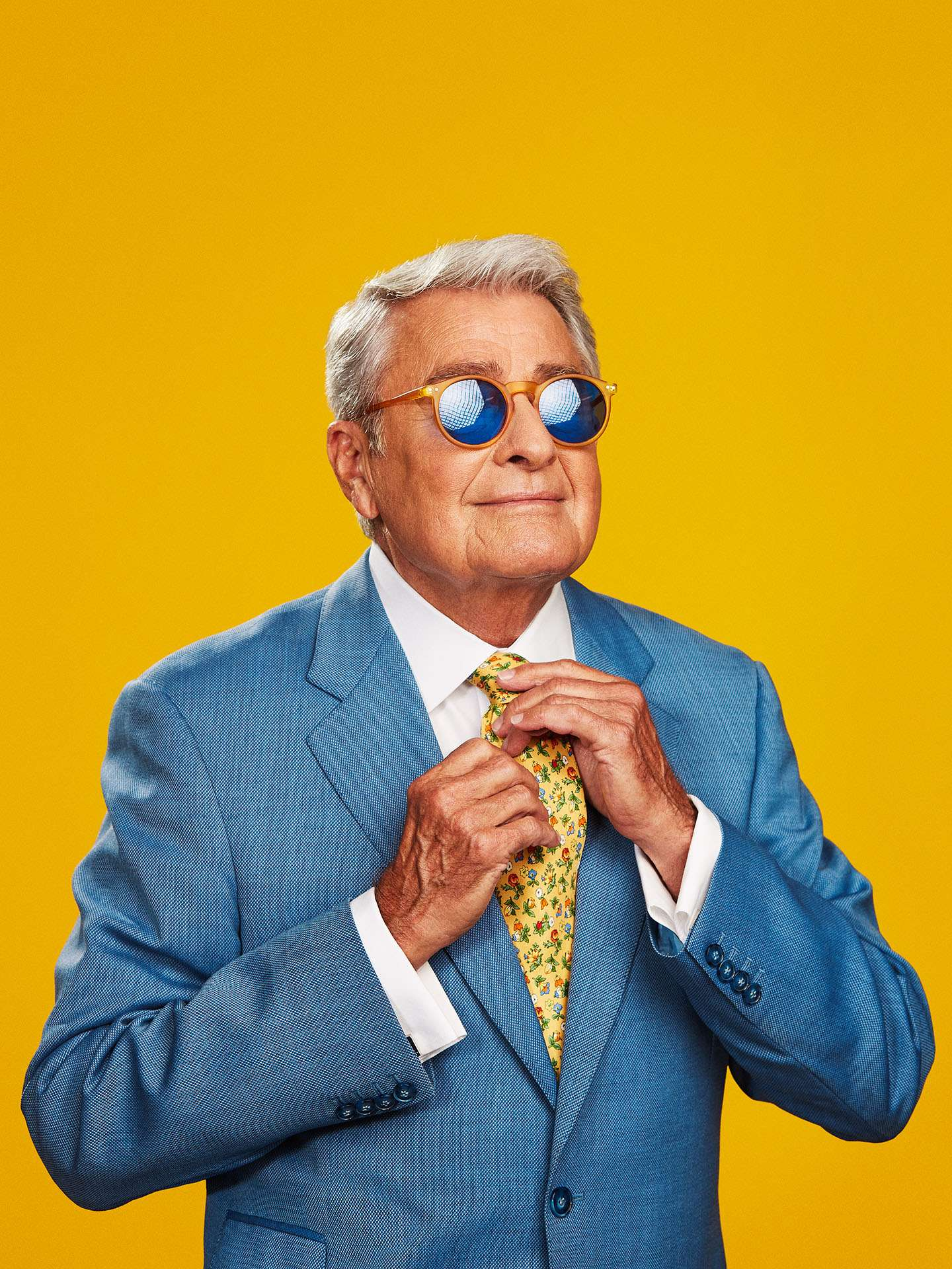 portrait of Michel Louvain adjusting his tie in light blue costume on bright yellow background by Jocelyn Michel for Voir magazine