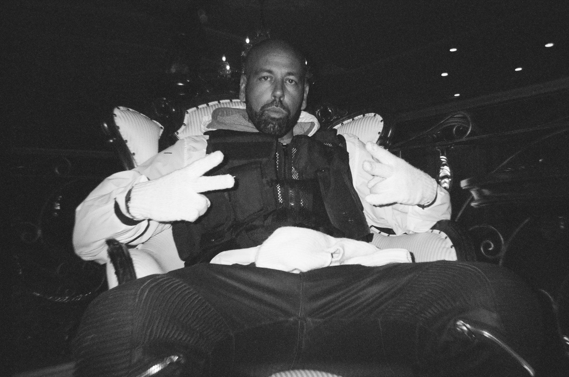 rapper Sinik sitting in chair legs spread wide for rapper Souldia music video Rouge Neige filmed by Les Gamins featuring Seth Gueko and Rick Pagano