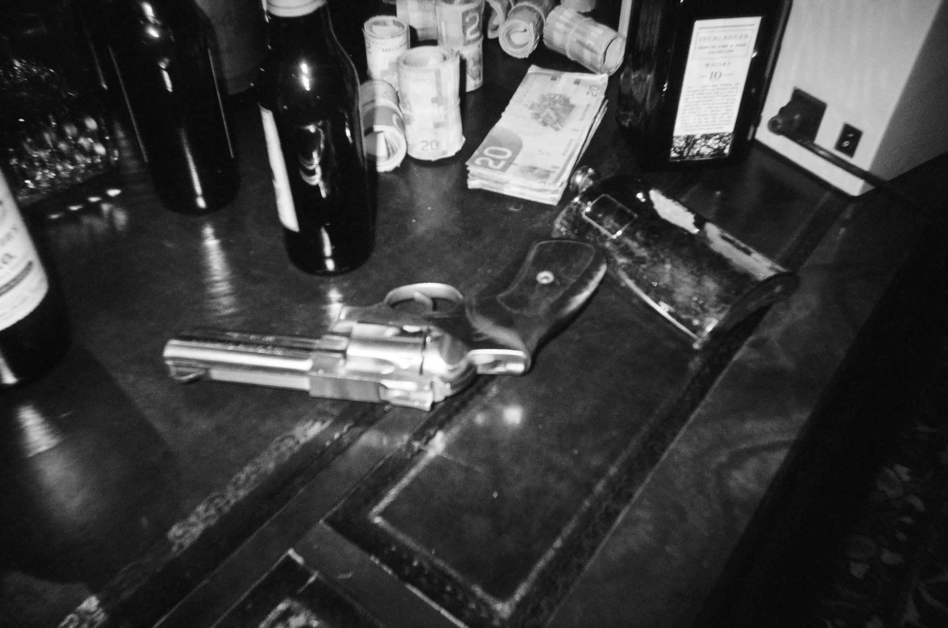 fake gun on table among empty alcohol bottles and dollar bills for rapper Souldia music video Rouge Neige filmed by Les Gamins featuring Sinik, Seth Gueko and Rick Pagano