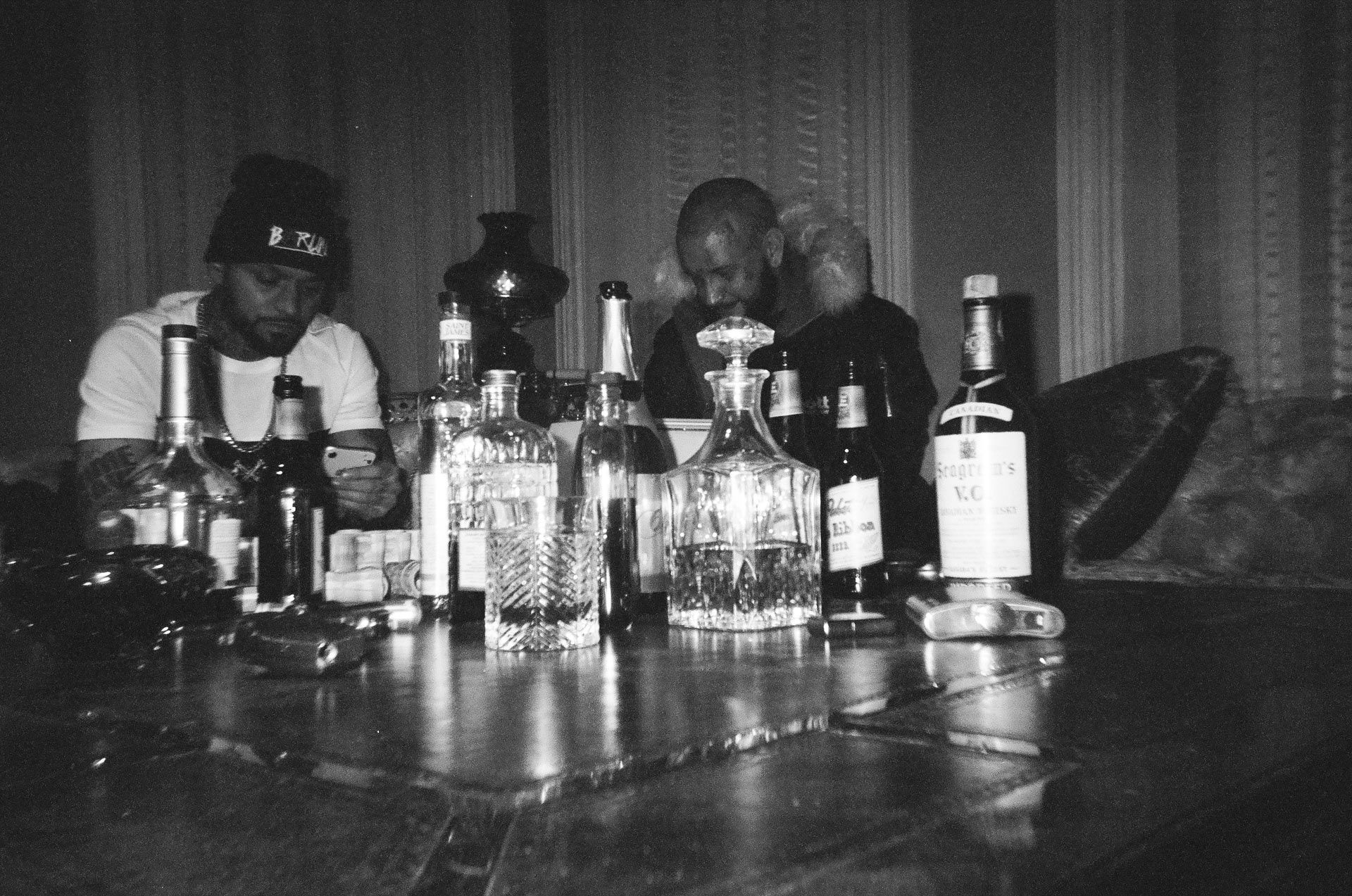 rapper Souldia and Seth Gueko sitting on couch looking at their phones with table layered with alcohol bottles and glasses for his music video Rouge Neige filmed by Les Gamins featuring Sinik and Rick Pagano