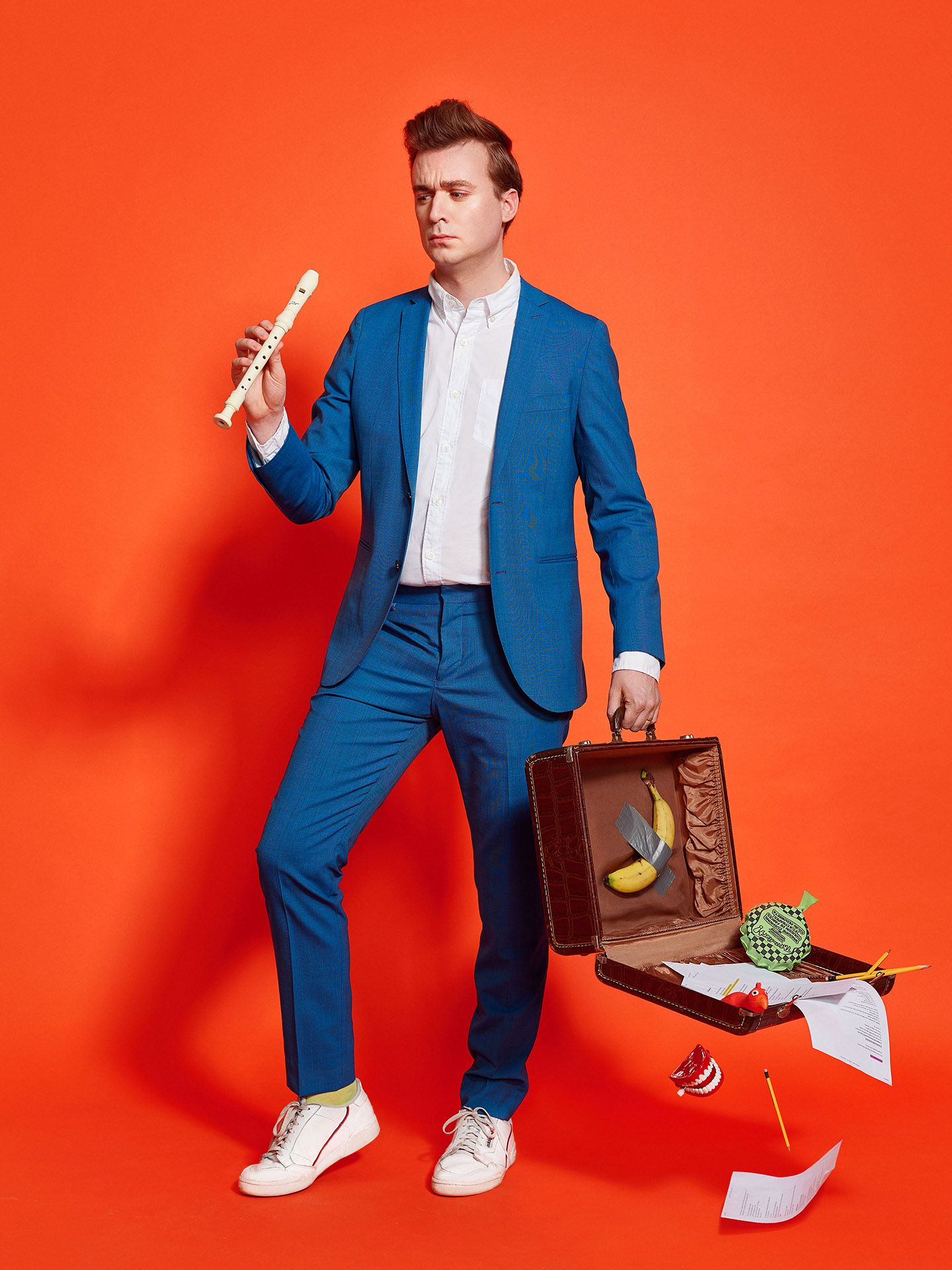 Photo of Arnaud Soly wearing a blue suit, a white shirt, white sneakers. He is holding a flute in one hand and a luggage that is open and from which are falling humor objects.