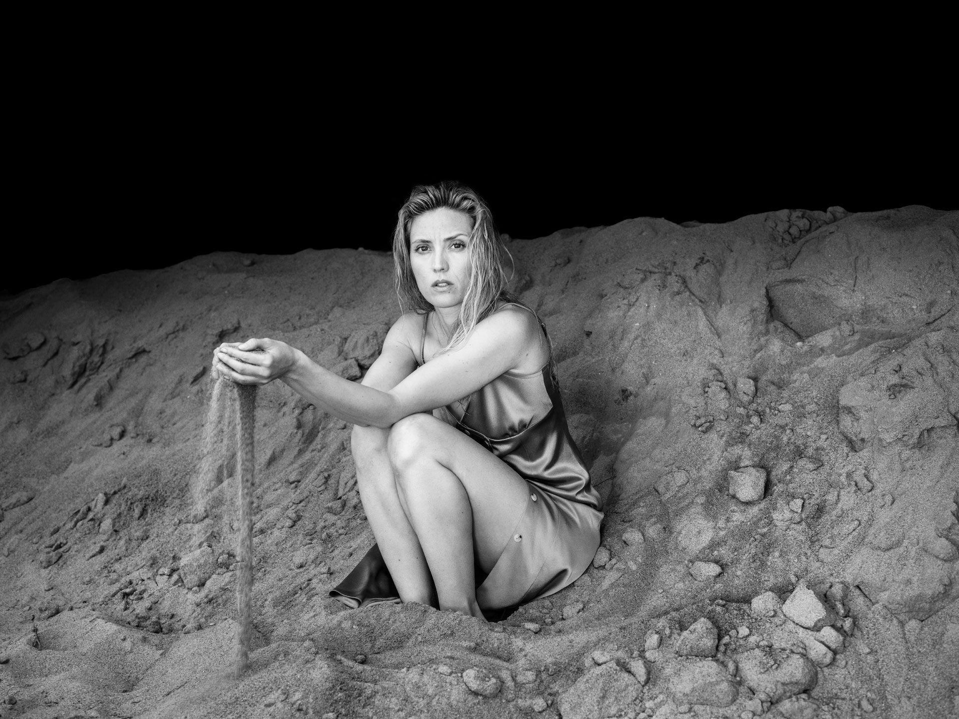 Evelyne Brochu sur un tas de sable portant une robe en soie dans l'obscurité.
