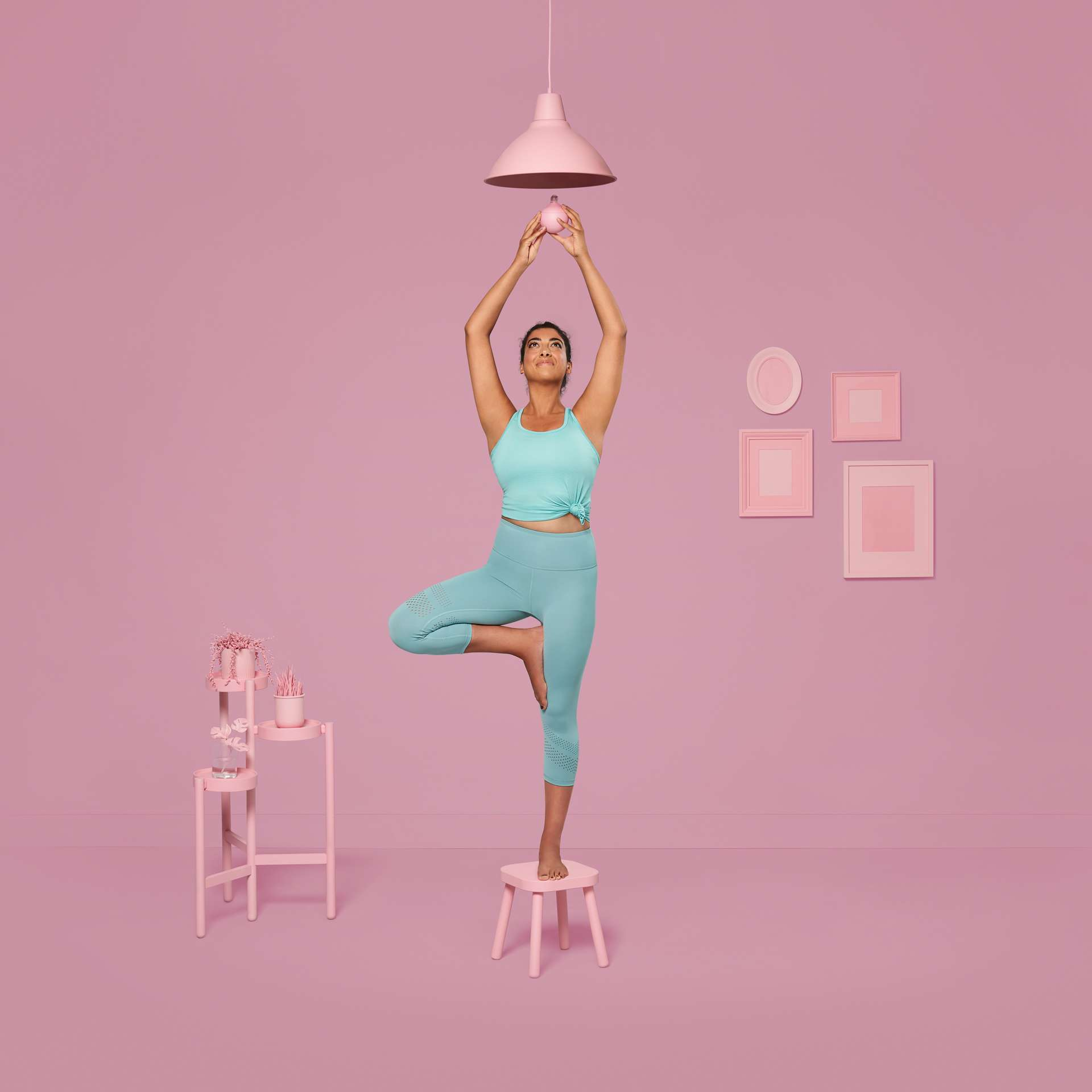white women in a tree yoga pose changing a lightbulb dressed in blue on pink background for YMCA by Jocelyn Michel