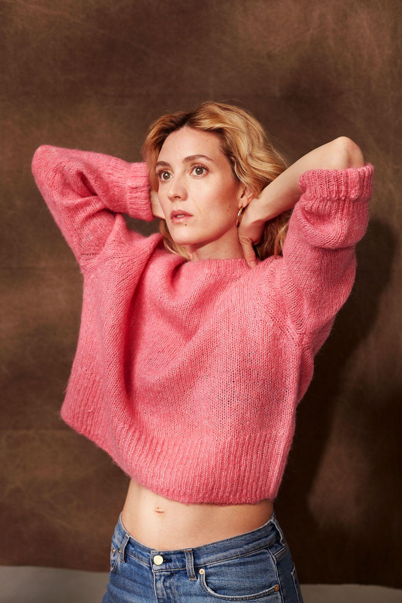 Evelyn Brochu en studio, portant un pull rose et un jean bleu, les bras en l'air.
