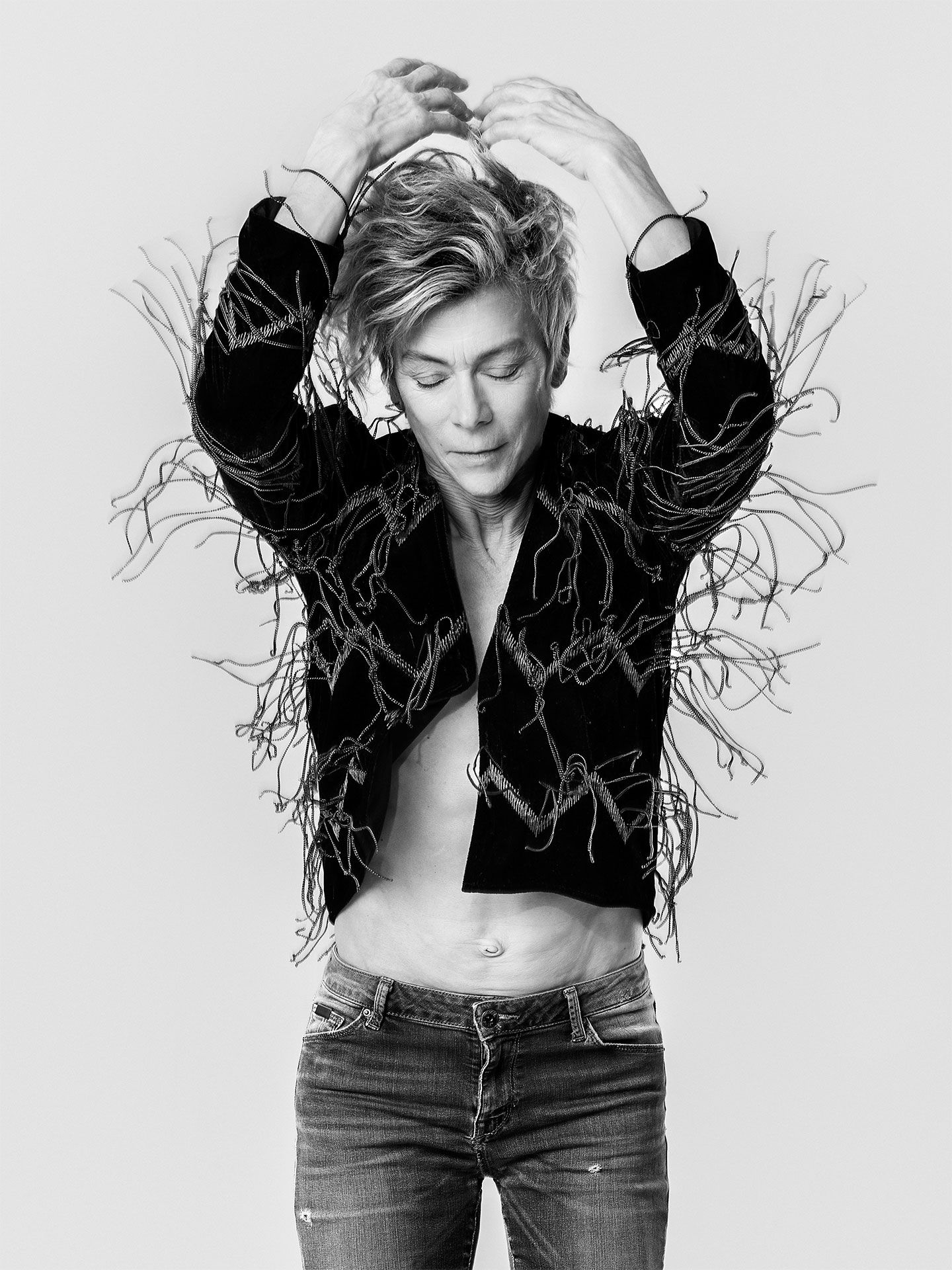 Black and white image of Louise Lecavalier in motion, arms up wearing a tasseled jacket.