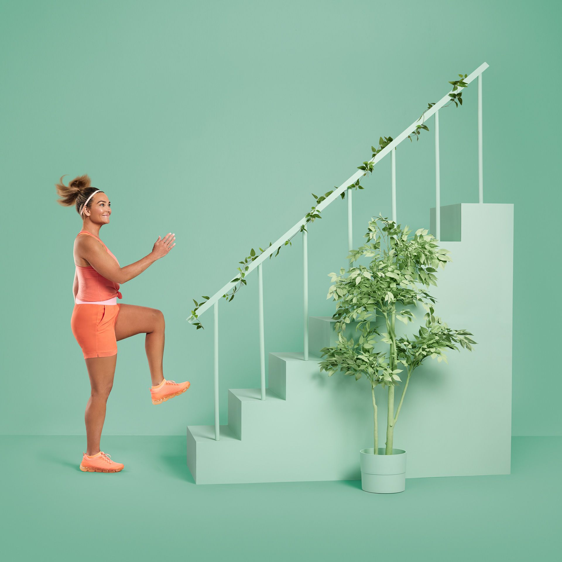 white women dressed in orange going up the stairs on green background for YMCA by Jocelyn Michel