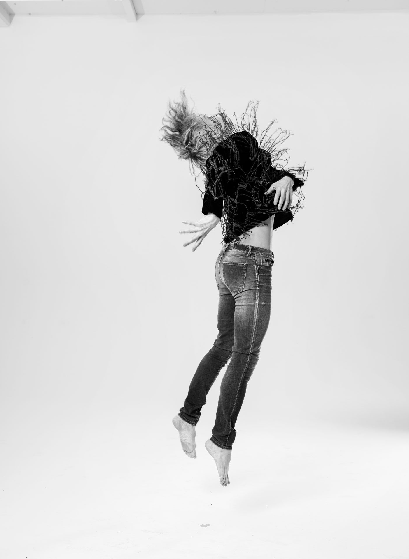 Full-length black and white photo of Louise Lecavalier jumping.