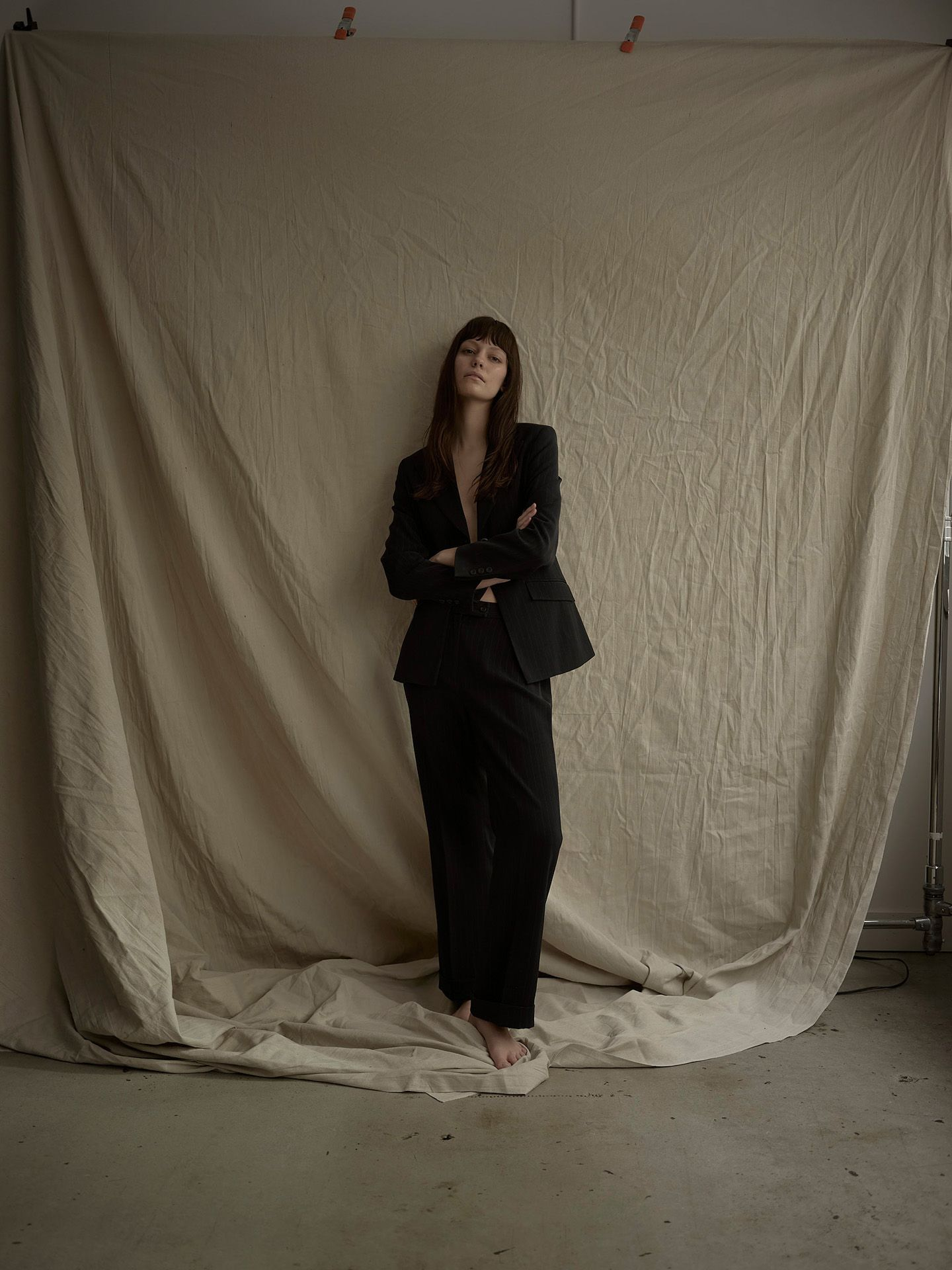 woman model wearing black suit pants and jacket on beige fabric background by Maxyme G Delisle for Mariane