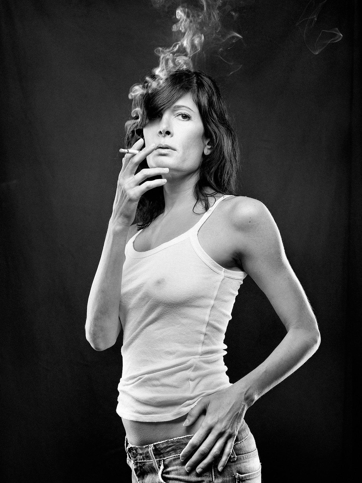 Portrait noir et blanc d'Anne-Marie Cadieux qui fume une cigarette.