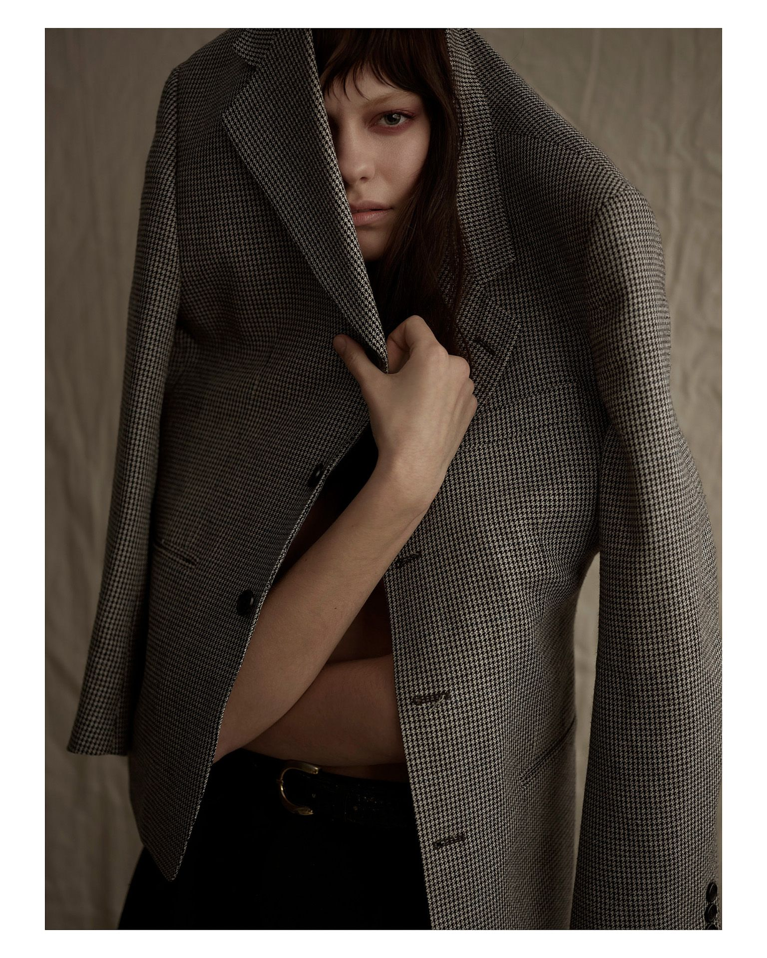 woman wearing black suit pants and checkered oversized suit jacket over her head looking at camera by Maxyme G Delisle for Mariane