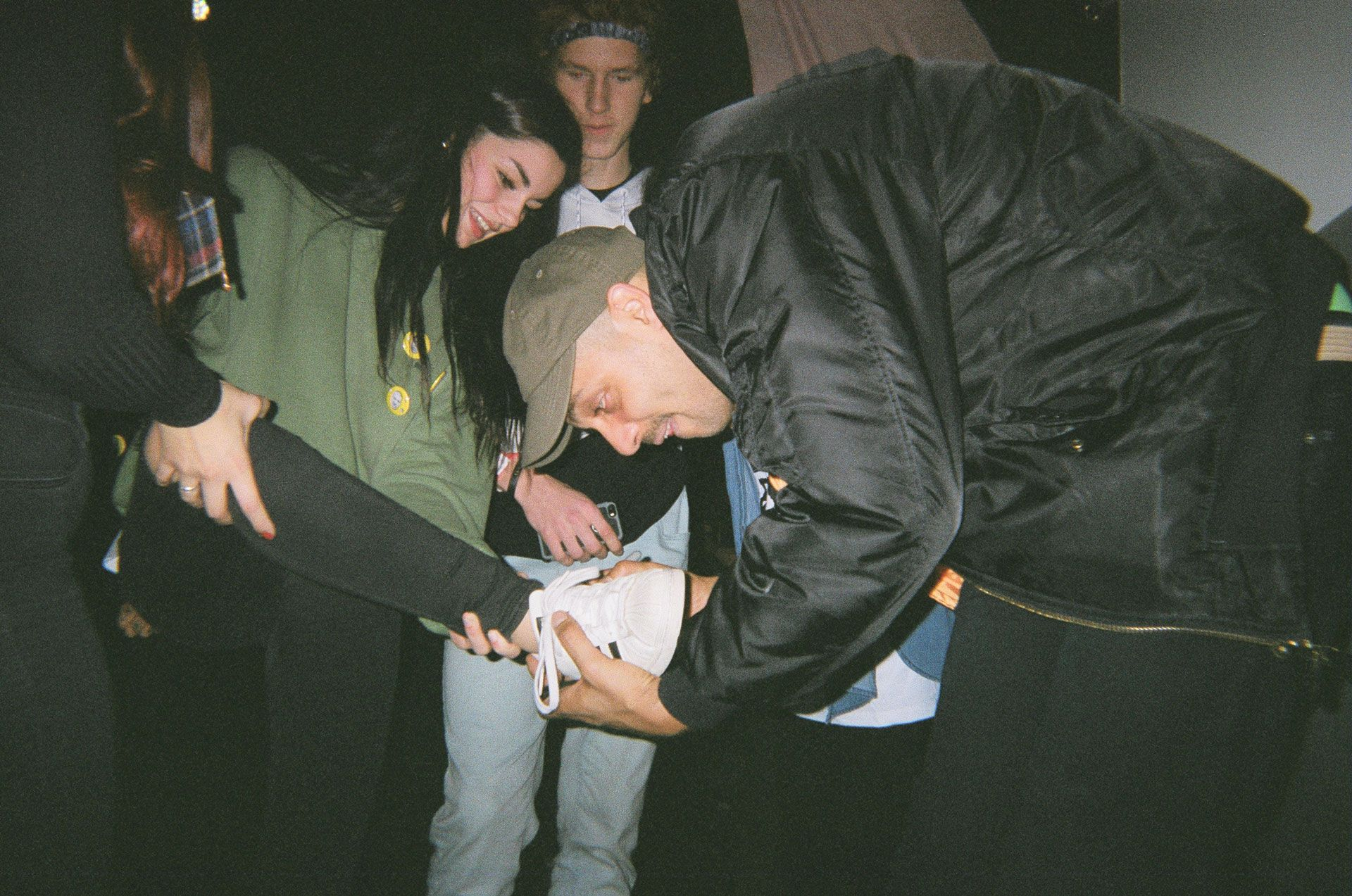 Alaclair Ensemble bandmember signing an autograph on a fan's shoe in behind the scenes of L'Osstidfilm documentary filmed by Vincent Ruel-Cote from Les Gamins about L'Osstidtour
