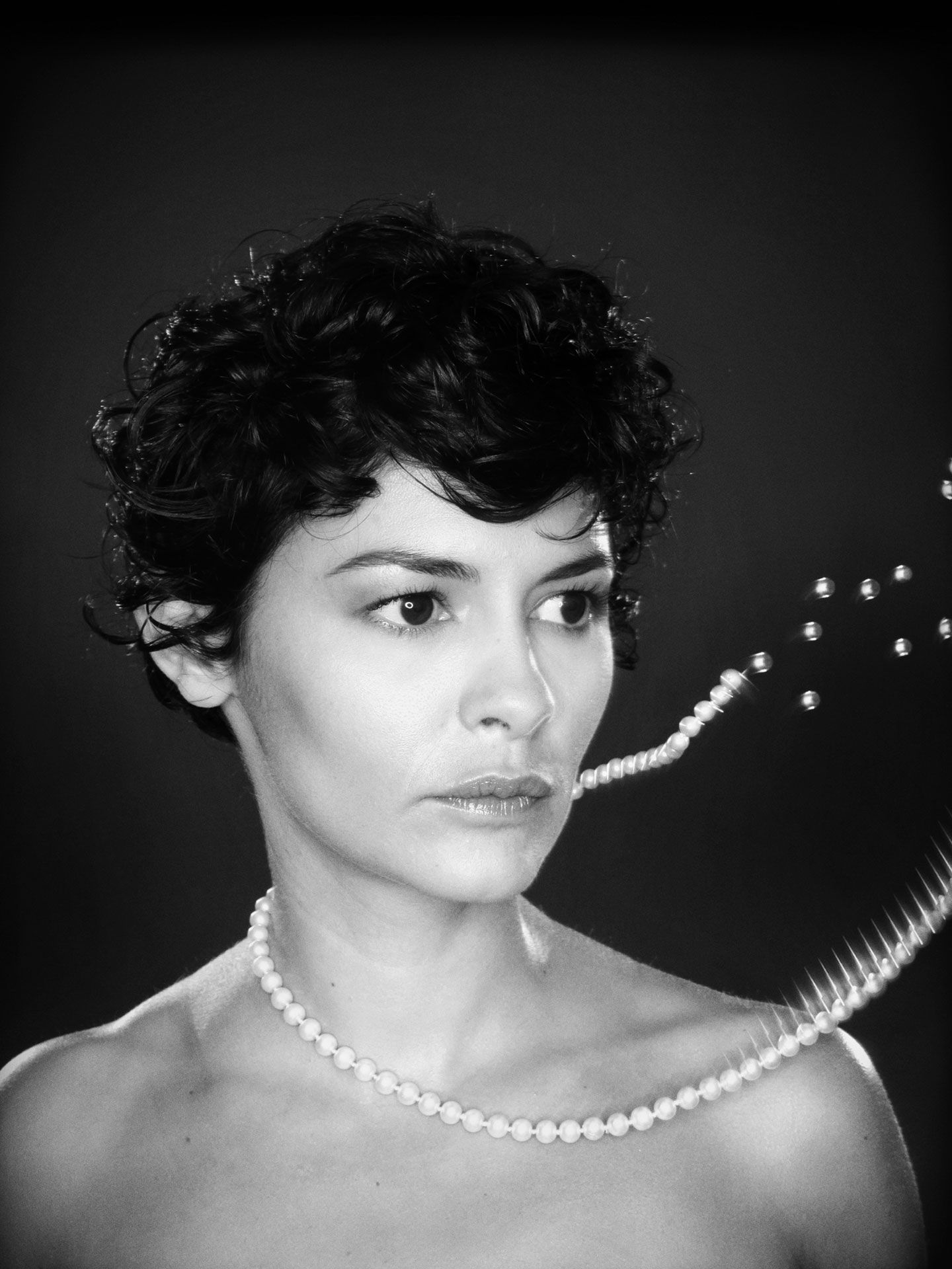 Black and white portrait of Audrey Tautou with a pearl necklace exploding and beads flying.
