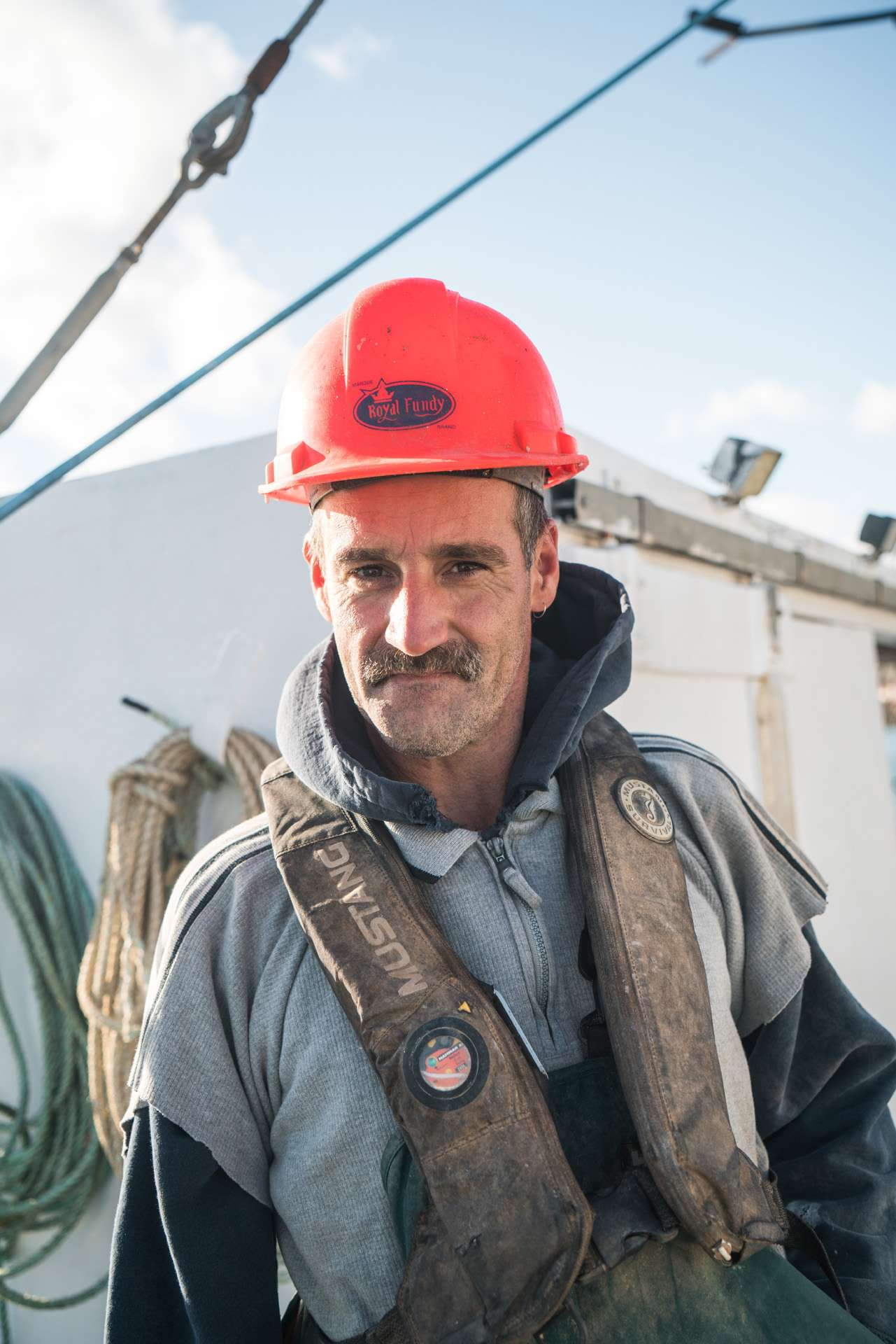 fisherman wearing red helmet smiling at camera by Bruno Florin for Ricardo Magazine