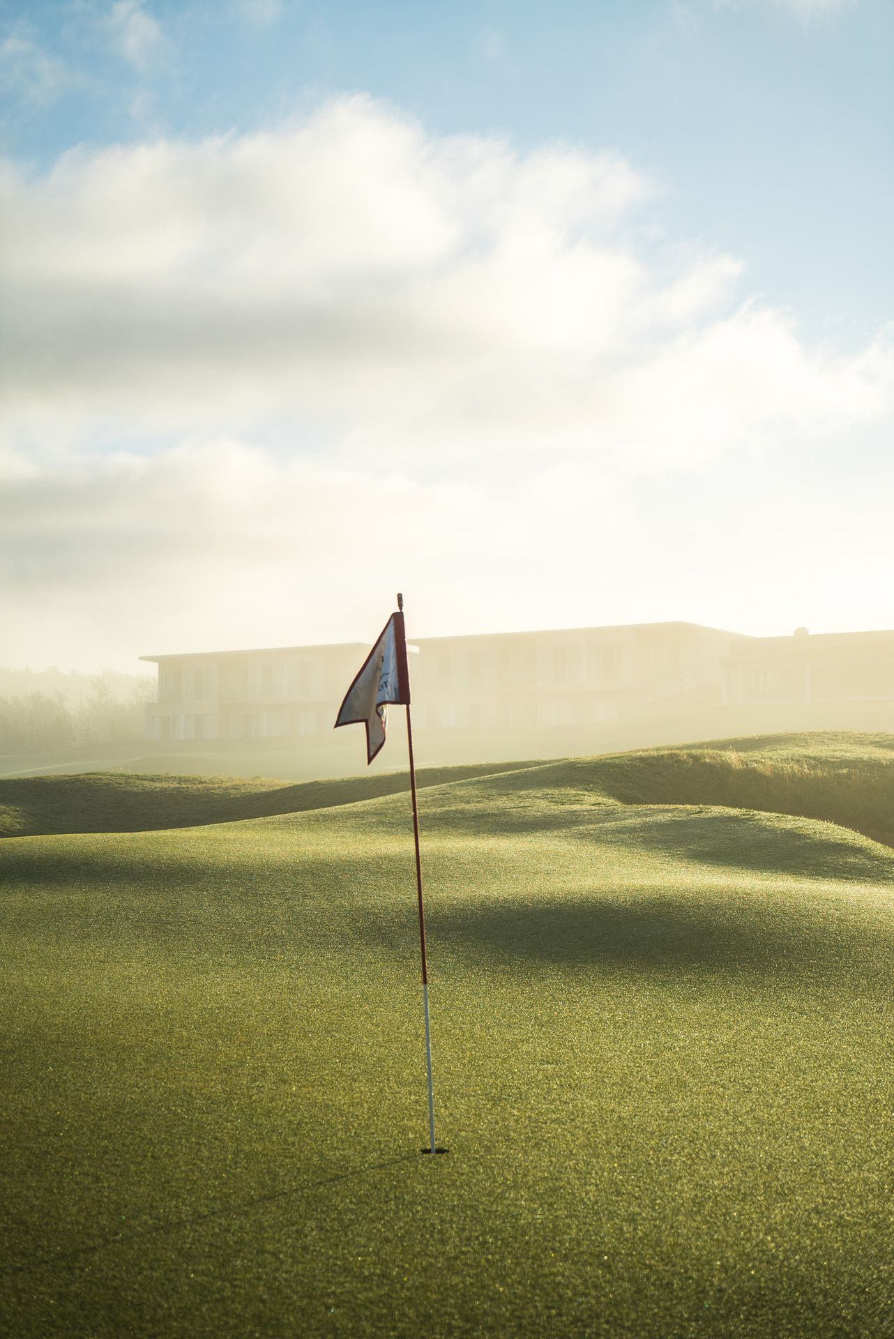 golf flag in early morning fog by Bruno Florin for Mercedes Magazine in Cabot Links