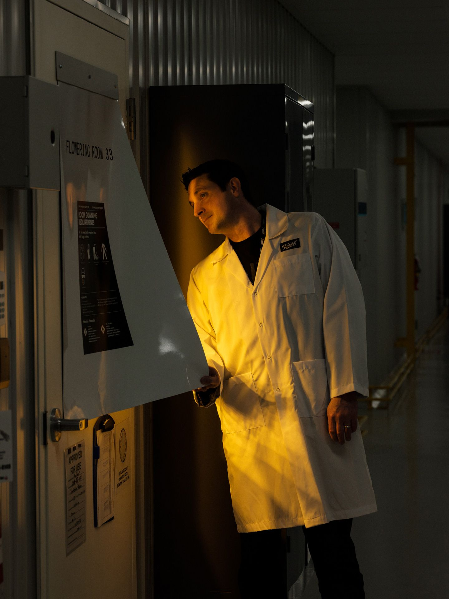 scientist looking in a growing tank illuminated by orange light by Alexi Hobbs at Tweed HQ for Bloomberg Businessweek