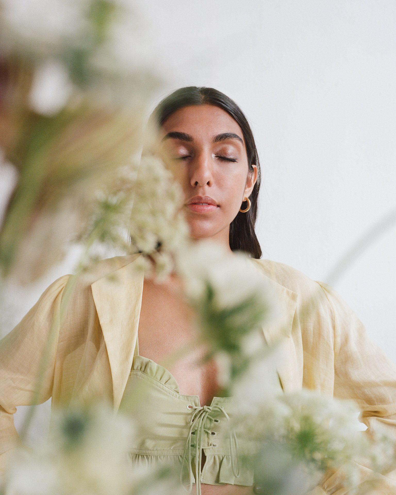 writer Rupi Kaur eyes closed behind plants by Oumayma B Tanfous for Vogue Espana
