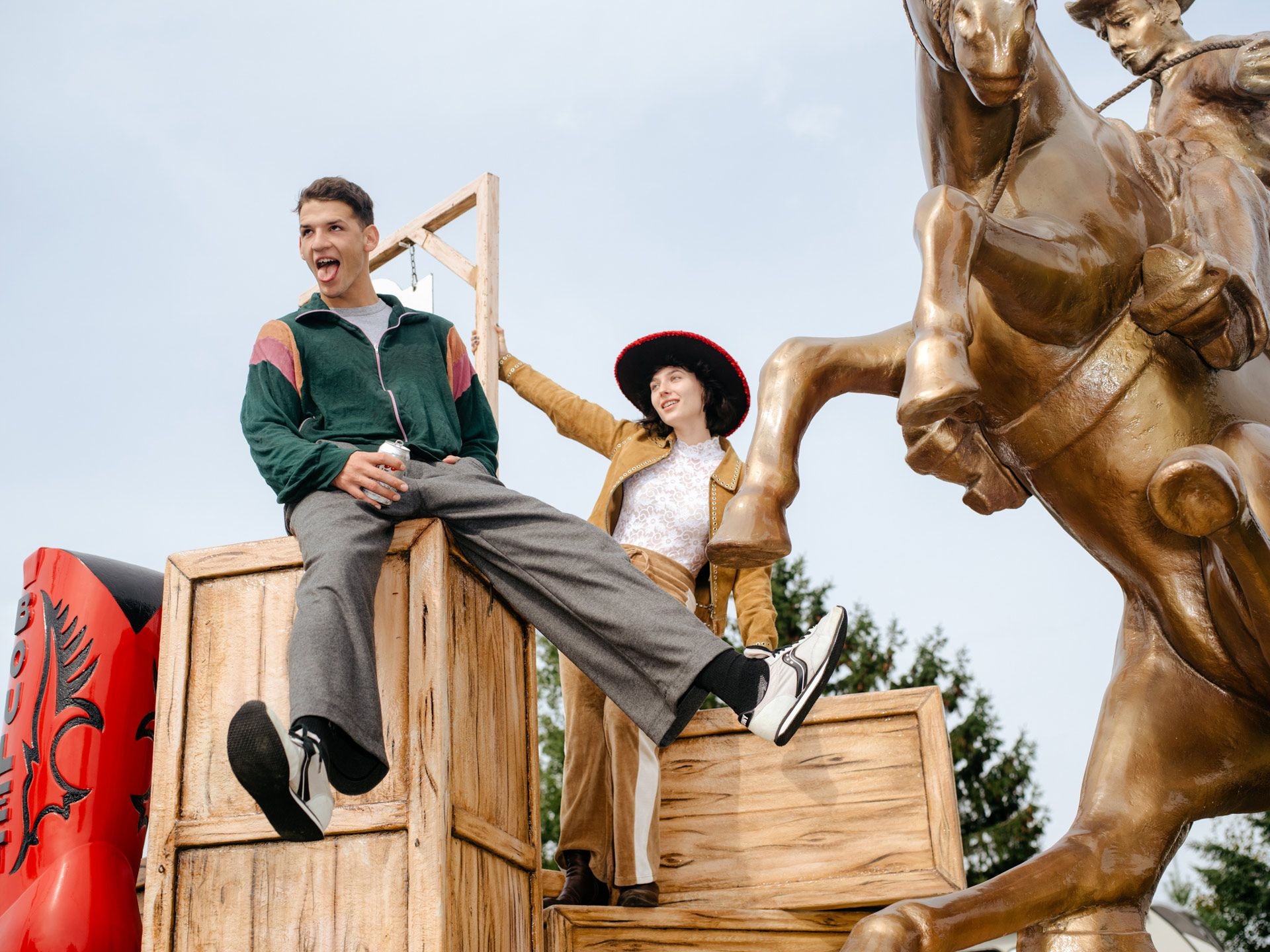 boy and girl posing on wood boxes next to cowboy statue by Alexi Hobbs for Larose Paris in St-Tite