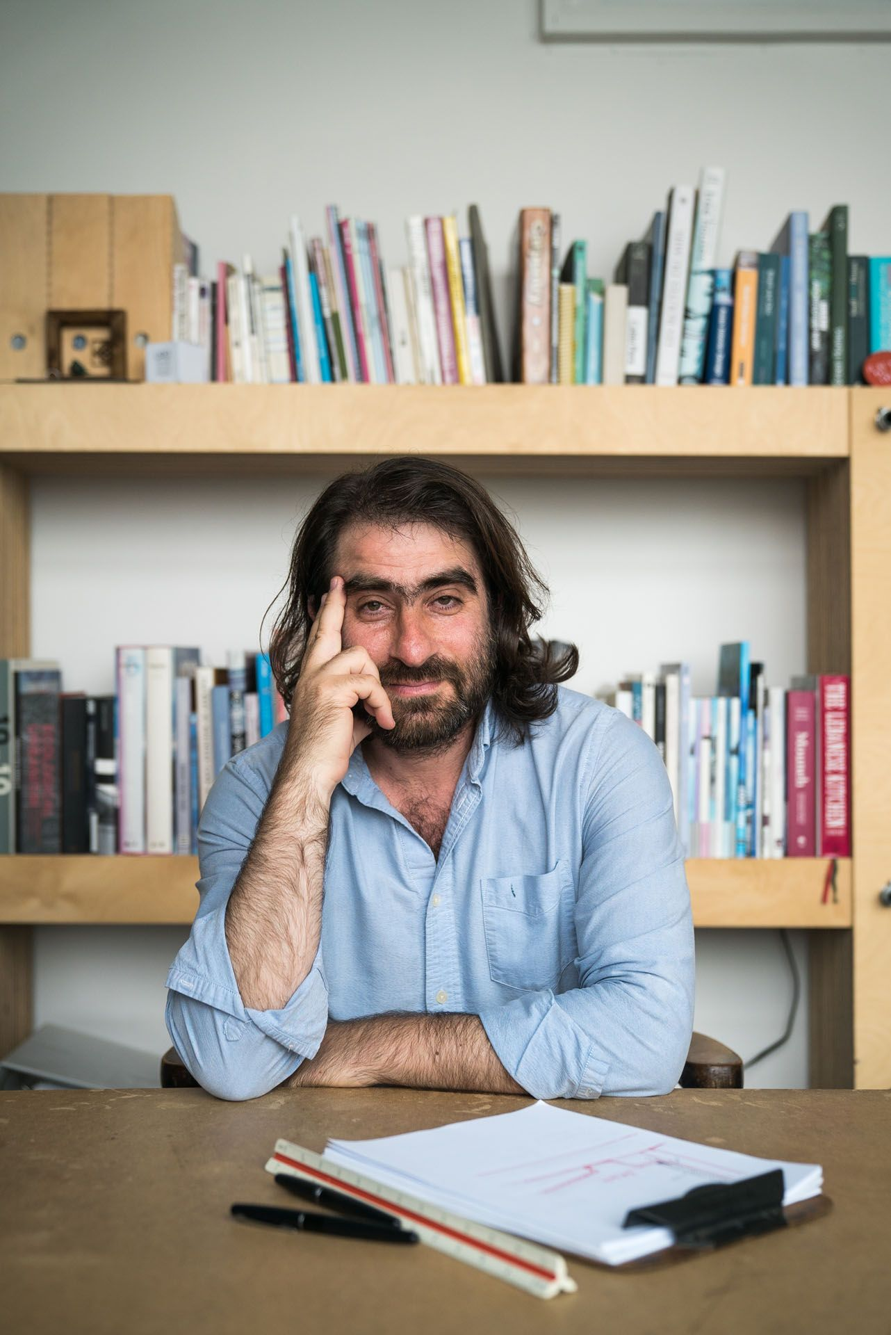 male writer long hair beard and unibrow sitting at desk in front of library looking at camera wearing light blue shirt by Bruno Florin for mile ex mille vie