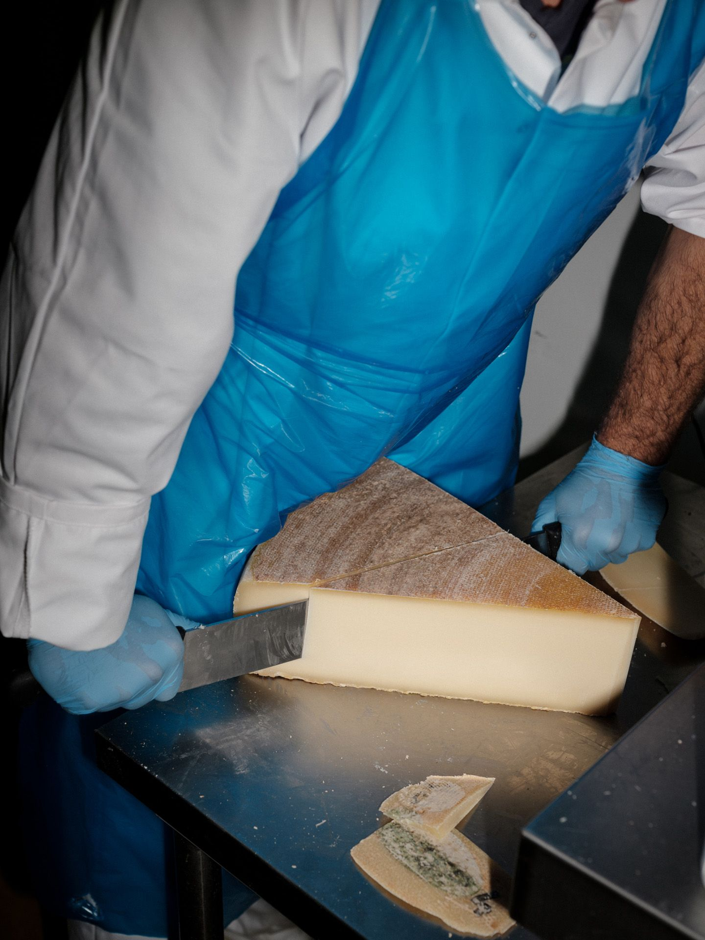 worker cutting huge piece of cheese for pasta by Alexi Hobbs in Auvergne for Reflets de France
