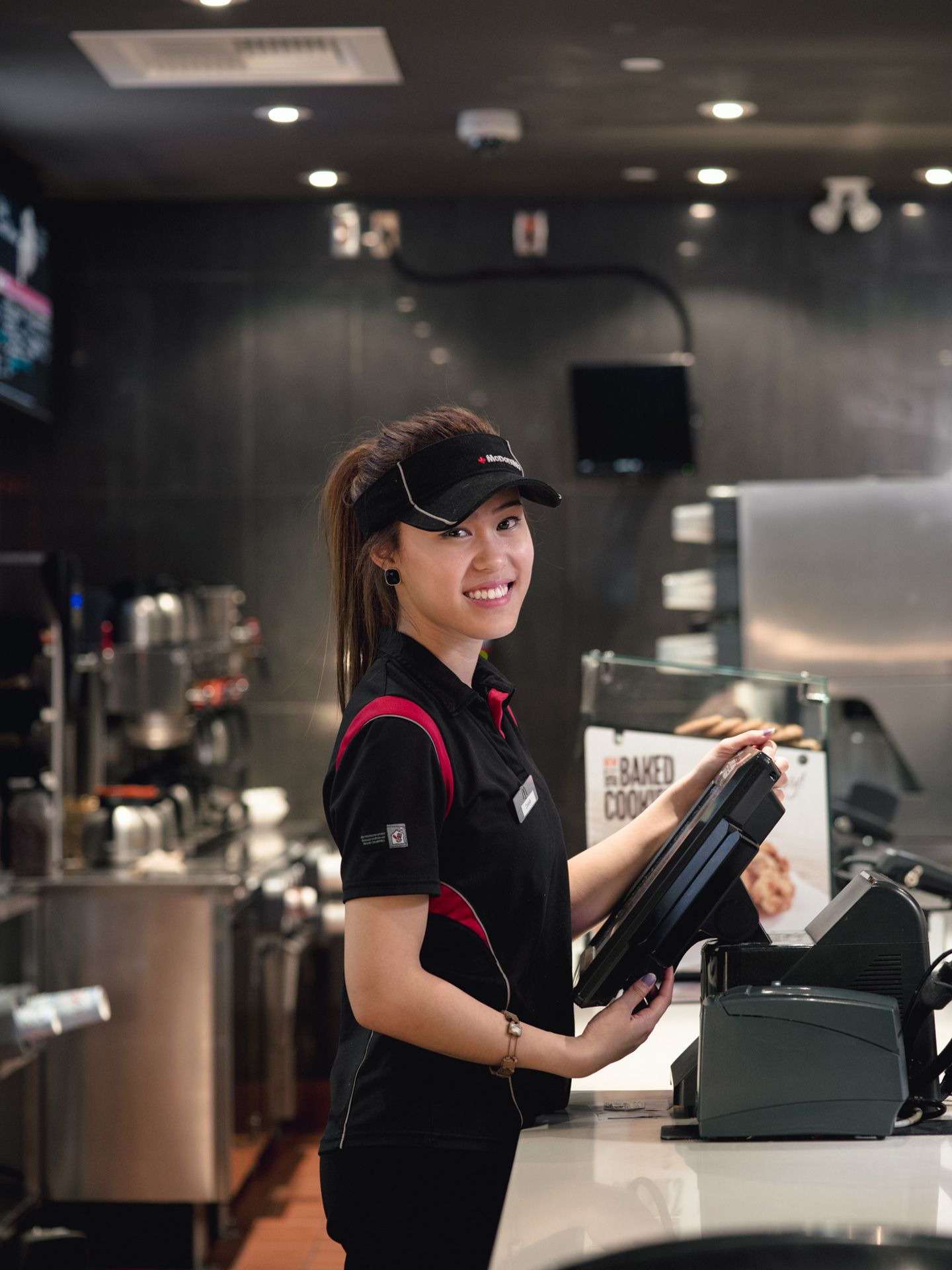 young asian female employee taking orders at the counter smiling at camera by Alexi Hobbs for McDonald's