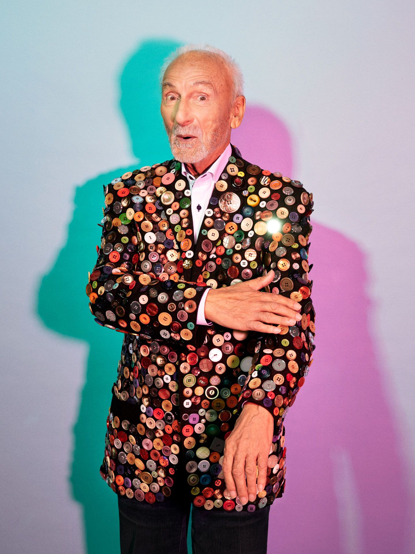 Portrait of Yvon Deschamps. He is wearing a suit covered with colored buttons, is making a funny surprised face. The light around him and background are turquoise and pink.