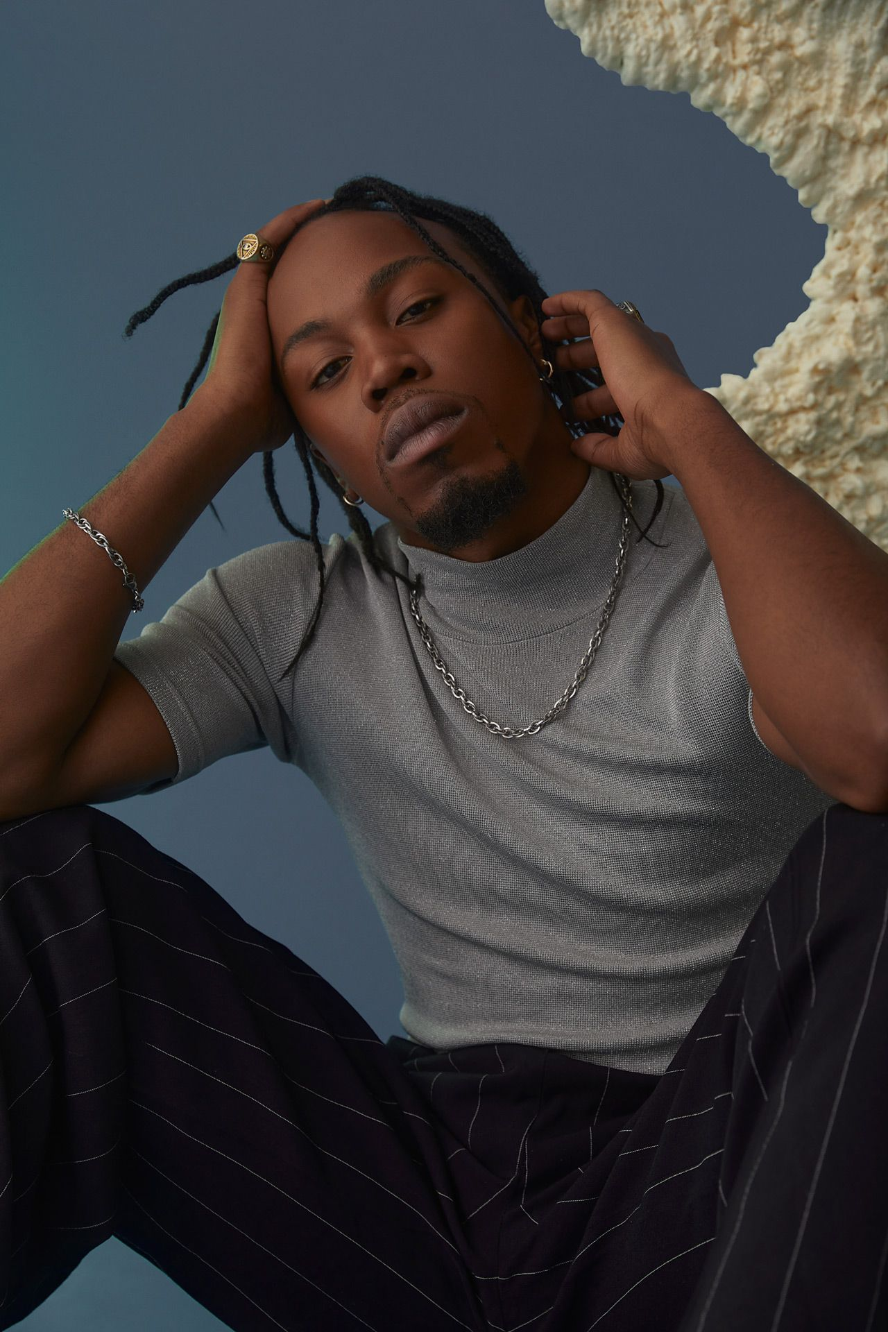 black male model sitting on the ground wearing grey shirt and striped black pants holding his head with one hand looking at camera on blue background photographed by Kelly Jacob for LEV