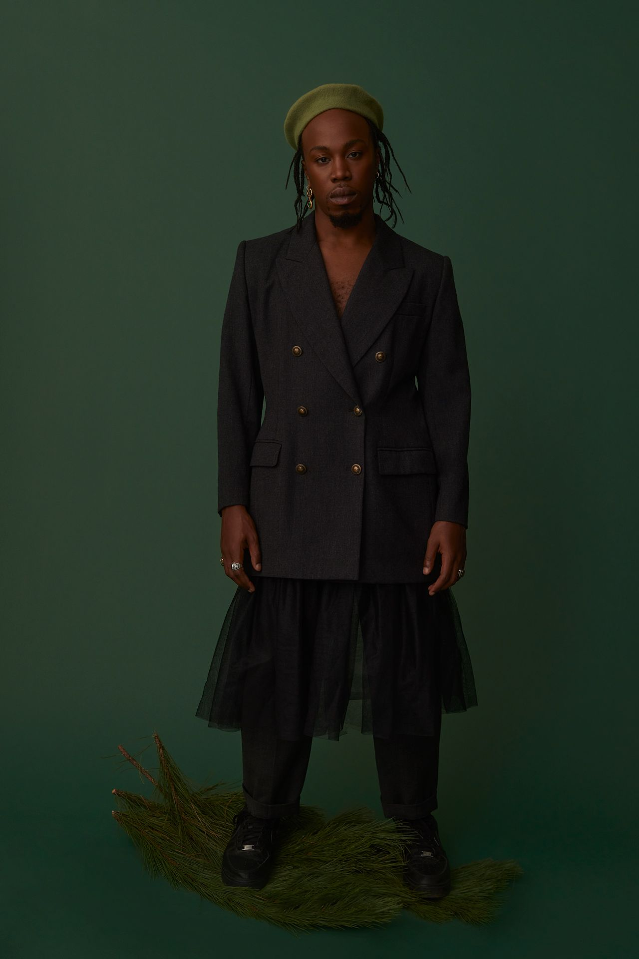black male model standing on pine branches wearing light green beret black suit jacket black skirt and black shoes looking at camera on dark green background photographed by Kelly Jacob for LEV