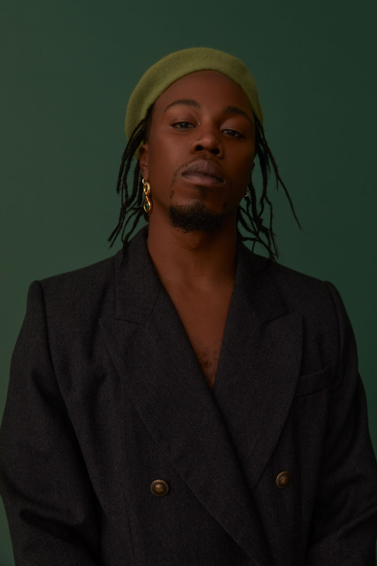 black male model wearing light green beret black suit jacket looking at camera on dark green background photographed by Kelly Jacob for LEV