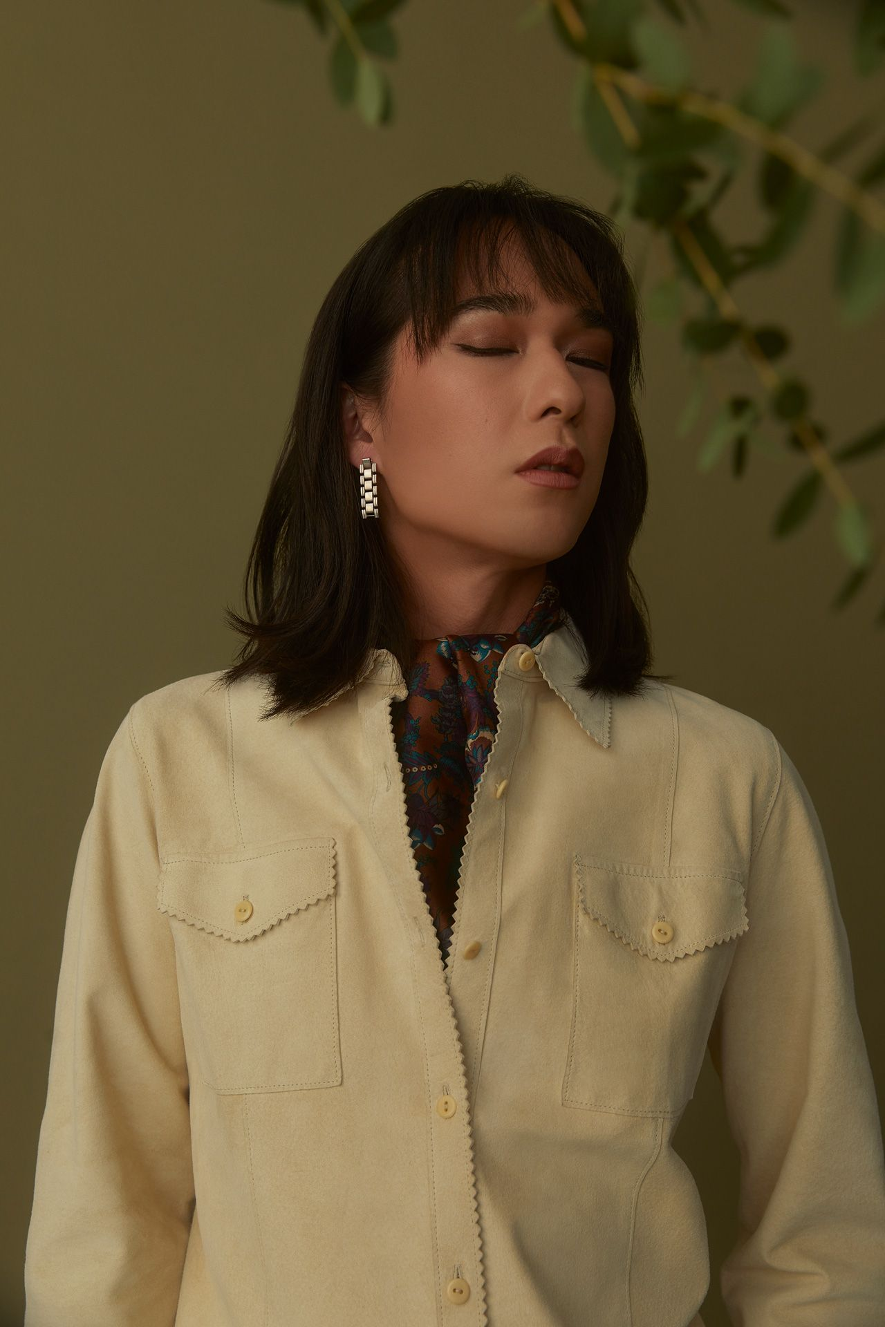 female model wearing beige suede button-up shirt with her eyes closed on dark green background photographed by Kelly Jacob for LEV