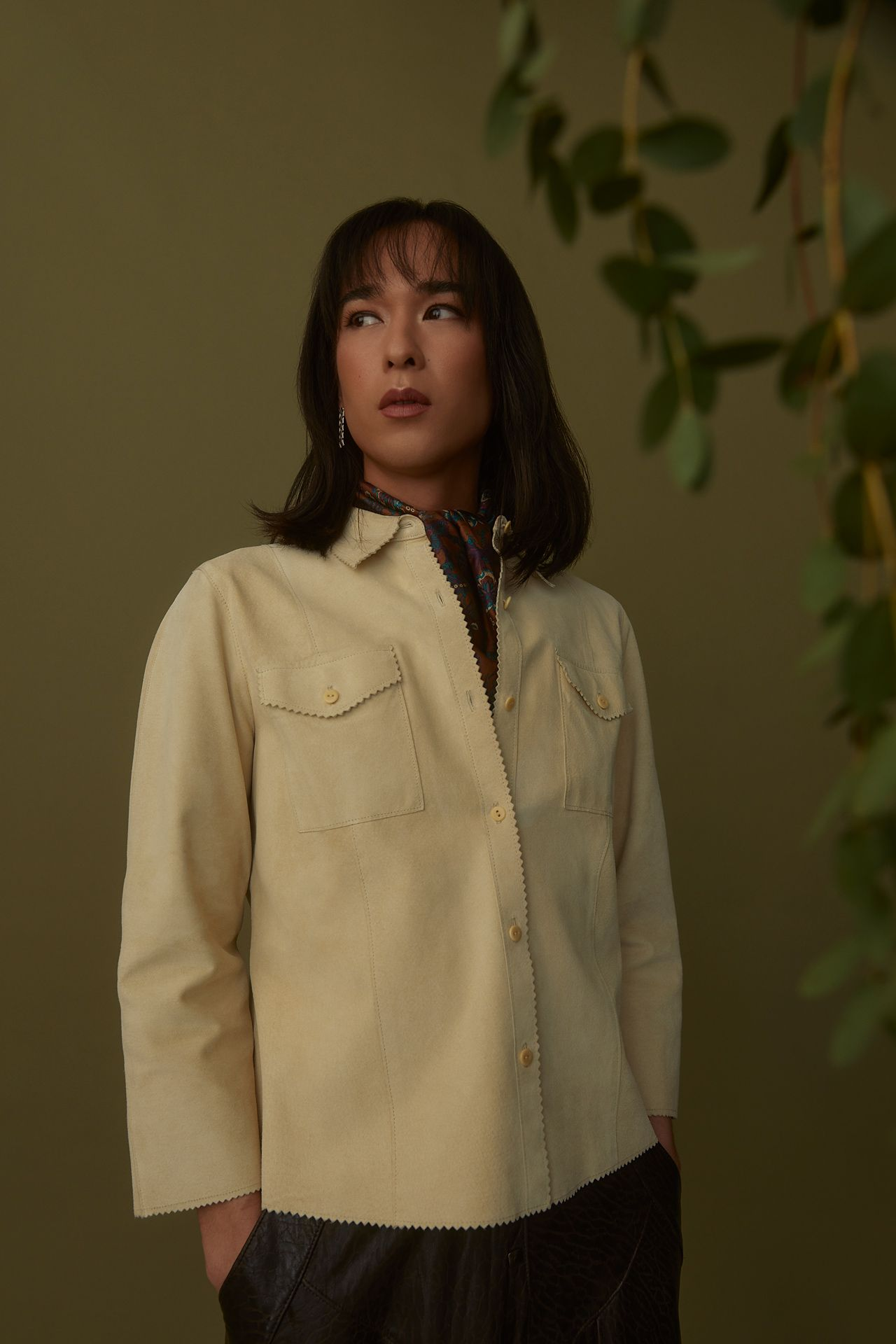 female model wearing beige suede button-up shirt and black pants with her hands in her pockets looking to the side on dark green background photographed by Kelly Jacob for LEV
