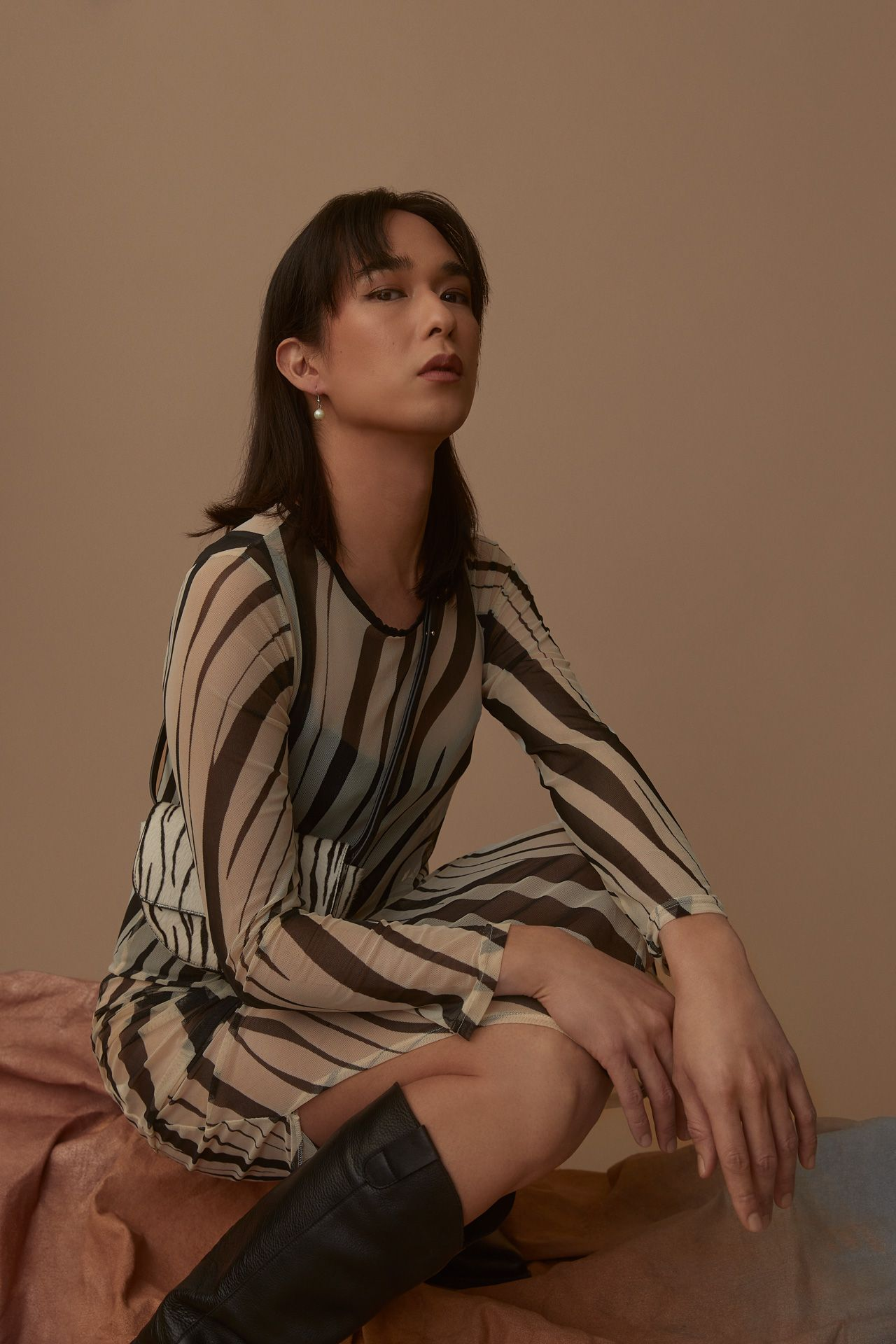 brown haired female model wearing see-through zebra dress and knee-high black leather boots looking at camera on beige background photographed by Kelly Jacob for LEV