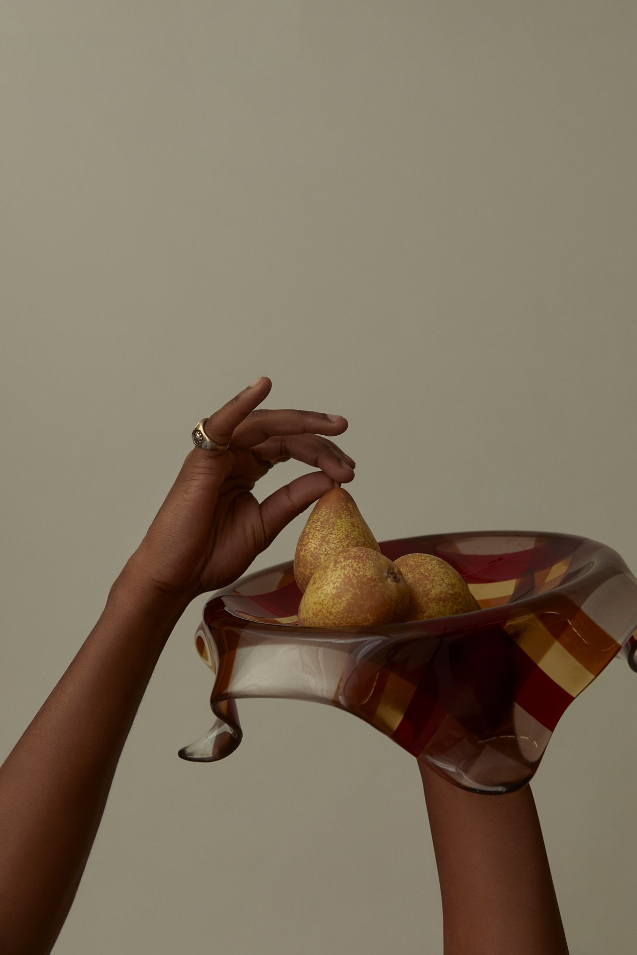 black hands holding plate of pears on light green background photographed by Kelly Jacob for LEV