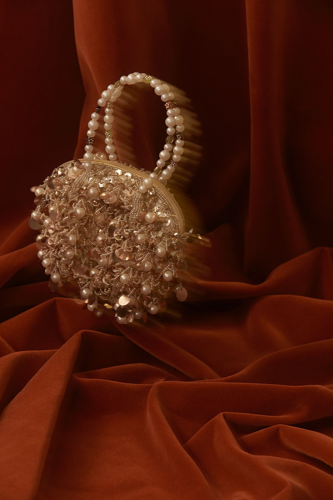 purse made out of beads and pearls on red suede fabric photographed by Kelly Jacob for LEV