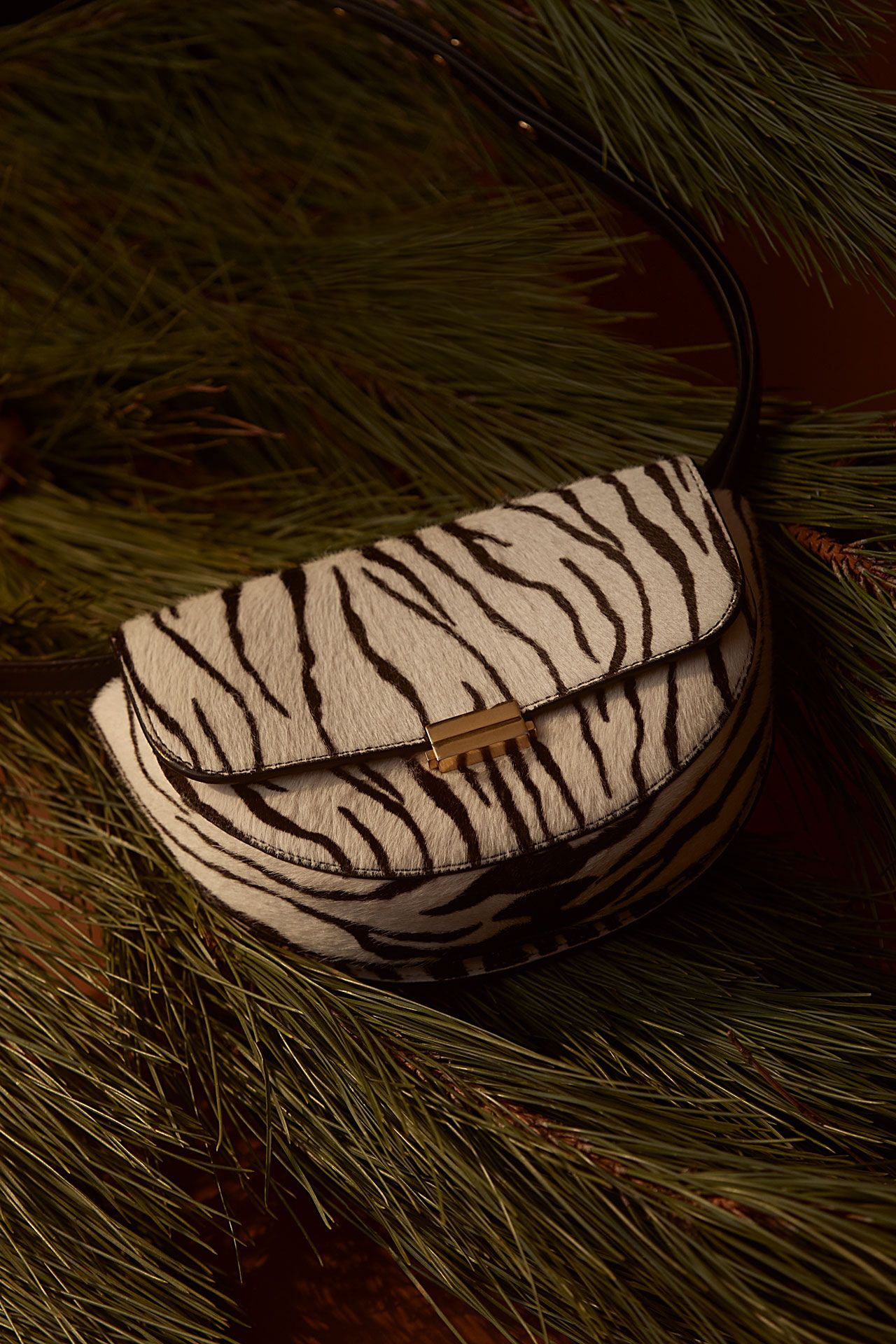 zebra fur covered purse on pine branches photographed by Kelly Jacob for LEV