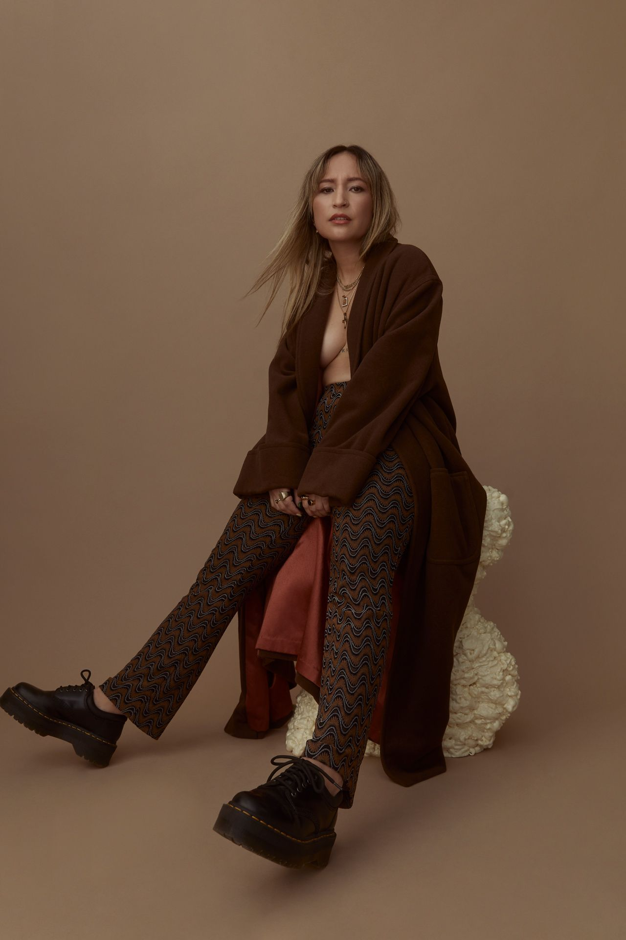 blonde female model sitting on rock wearing long large brown coat with wavy patterned shirt and platform doc martens looking at camera on beige background photographed by Kelly Jacob for LEV