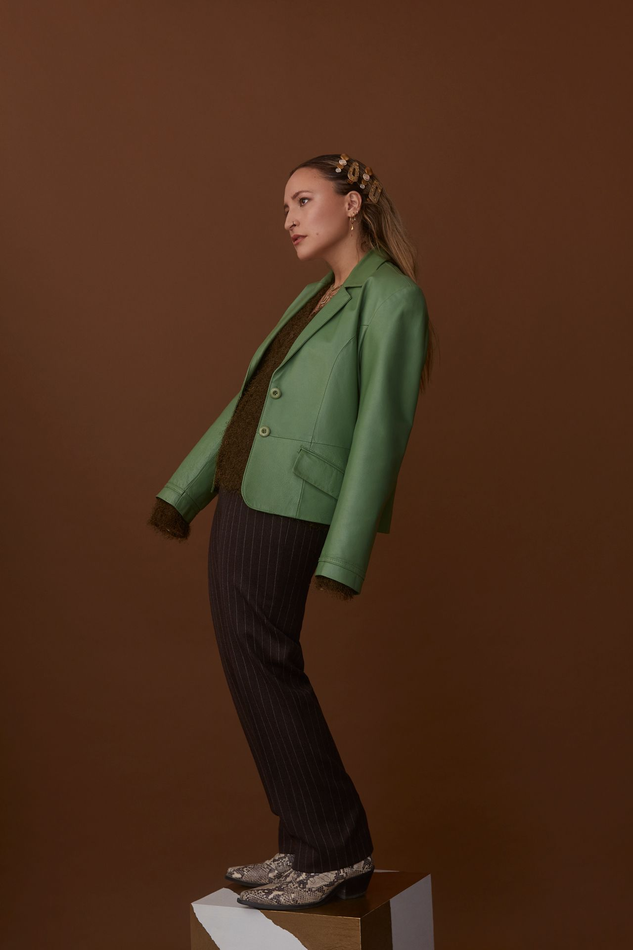 female model standing on block lightly leaning back wearing bright green leather jacket brown sweater fine-stripped black pants and snake skin shoes on brown background photographed by Kelly Jacob for LEV