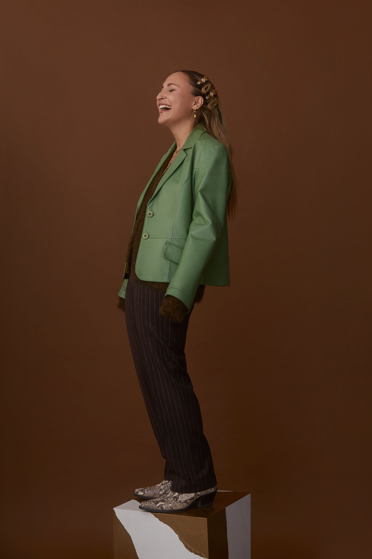 female model standing on block lightly leaning back and laughing wearing bright green leather jacket brown sweater fine-stripped black pants and snake skin shoes on brown background photographed by Kelly Jacob for LEV