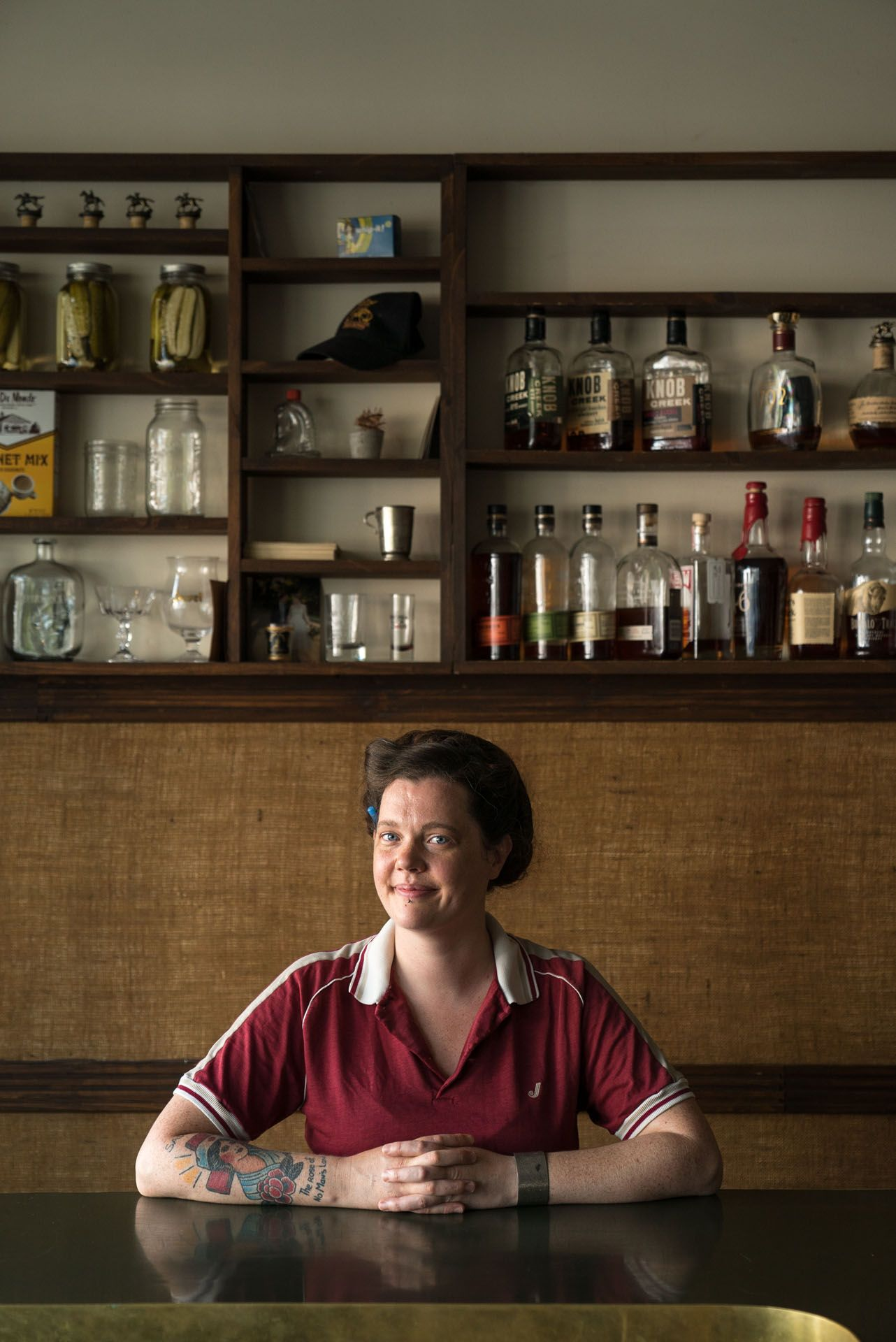 female bar owner sitting at table in front of wall with bottles by Bruno Florin for mile ex mille vie