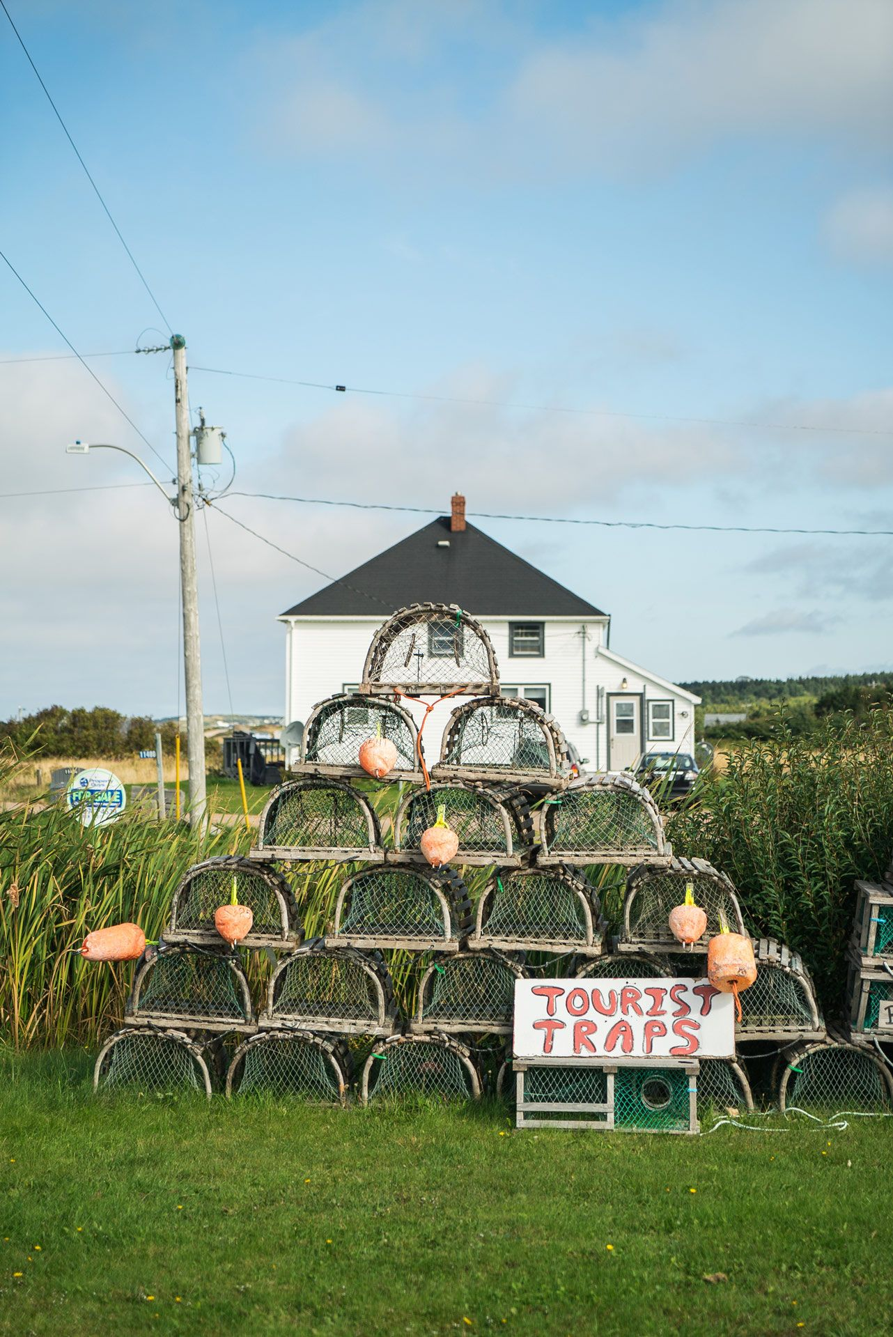 pile of crabs traps with 'tourist traps' sign by Bruno Florin for Mercedes Magazine