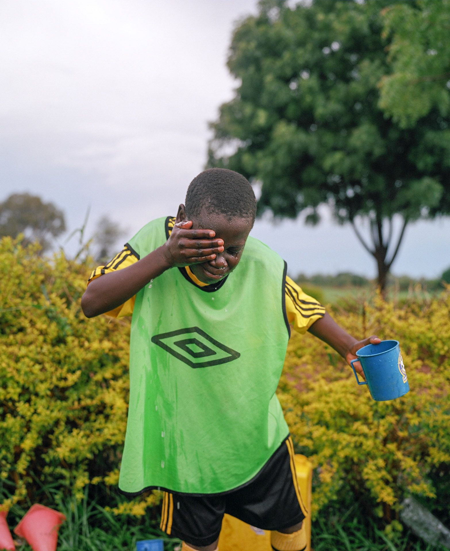 young black boy rinsing his face with water by Alexi Hobbs in Uganda for Football for good with Sportsnet