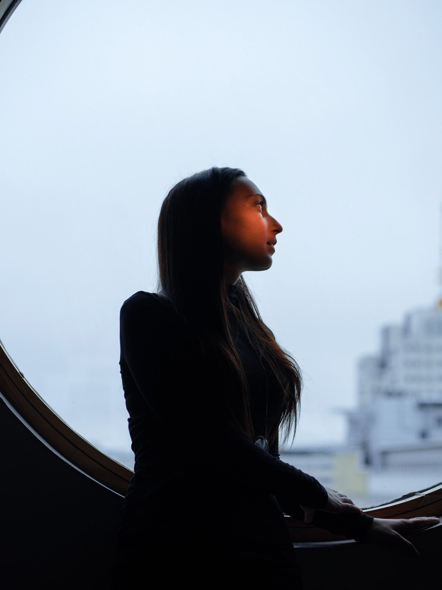 portrait of woman sitting on round window under orange light by Alexi Hobbs for WSP